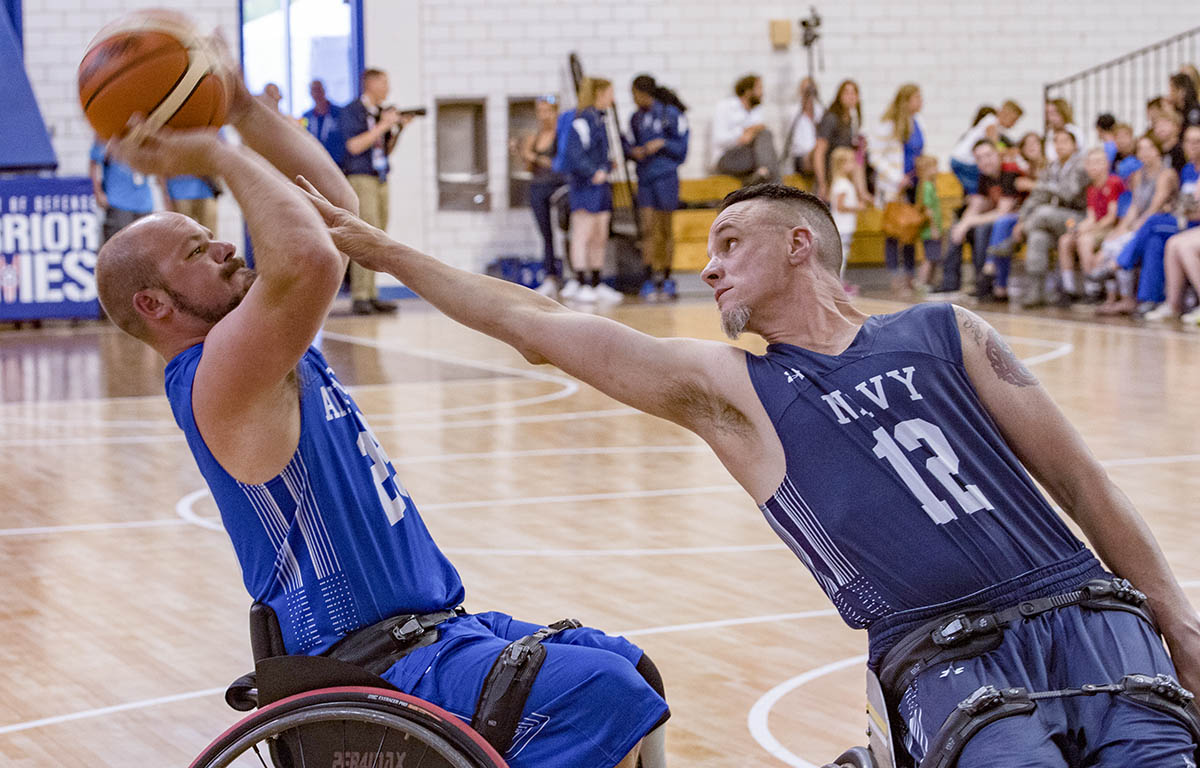 Veteran Russel Logan of Team Air Force attempts a shot while being blocked by U.S. Navy Command Master Chief Richard Curtis of Team Navy during a DoD Warrior Games wheelchair basketball game, June 4, 2018, at the U.S. Air Force Academy in Colorado Springs, Colorado. The Warrior Games are an annual event, established in 2010, to introduce wounded, ill and injured service members to adaptive sports as a way to enhance their recovery and rehabilitation. (Staff Sgt. Carlin Leslie/DoD)