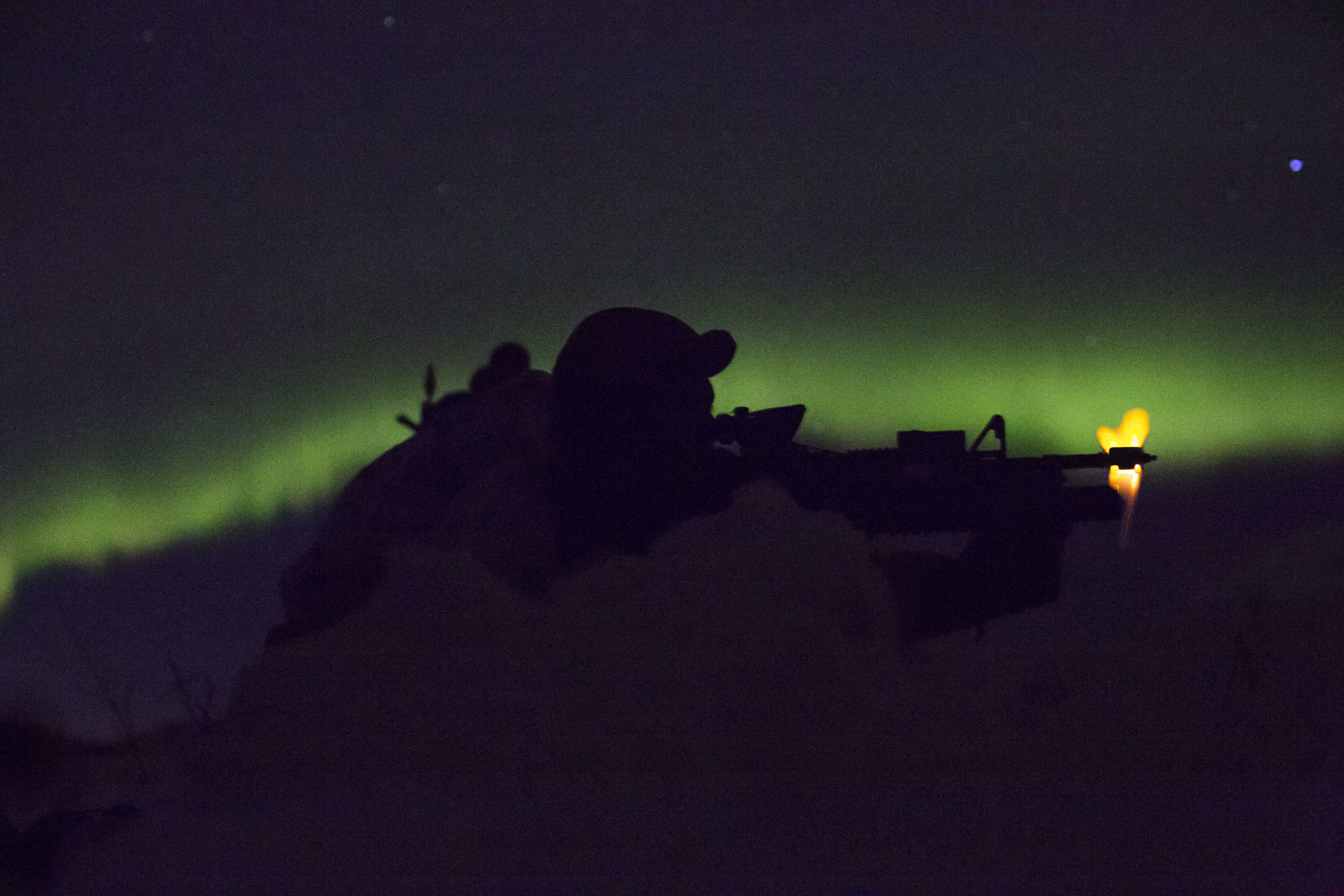Marine with Marine Rotational Force-Europe conducts a mountainous assault on enemy position as the northern lights shine above during the field training exercise portion of Exercise White Claymore near Bardufoss, Norway, February 15, 2018. White Claymore is a U.K. Royal Marines-led training in northern Norway that focuses on winter warfare including training on movement in adverse terrain and over snow, and training in defensive and offensive operations in winter conditions. (Staff Sgt. Marcin Platek/Marines)