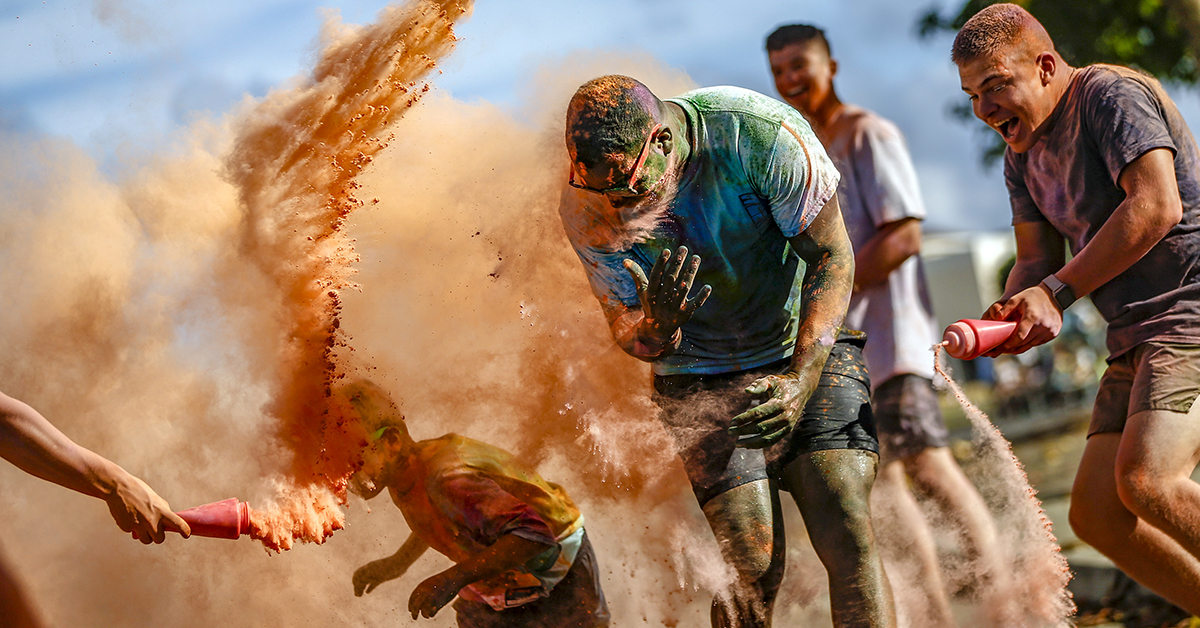 Runners get sprayed with colored powder during the 1st Battalion, 3rd Marine Regiment (1/3) 5K Color Dash, aboard Marine Corps Base Hawaii, Aug. 18, 2018. U.S. Marines with 1/3, held a 5K Color Dash where volunteers showered racers with colored powder while also giving participants a scenic route near Fort Hase Beach. (Sgt. Aaron S. Patterson/Marine Corps)