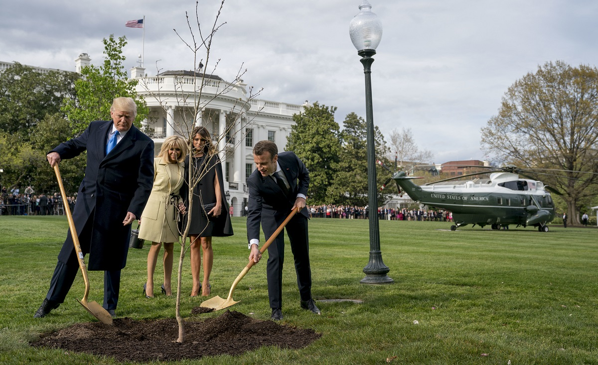 First lady Melania Trump, second from right, and Brigitte Macron, second from left, watch as President Donald Trump and French President Emmanuel Macron participate in a tree planting ceremony on the South Lawn of the White House in Washington, Monday, April 23. (Andrew Harnik/AP)