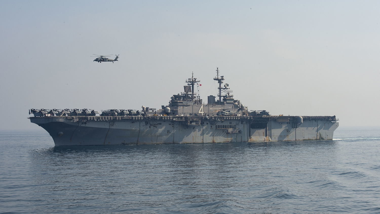 A SH-60 Sea Hawk flies over the amphibious assault ship USS Boxer (LHD 4) during a vertical replenishment-at-sea on July 19, 2019, in the Arabian Gulf. (Mass Communication Specialist 3rd Class Keypher Strombeck/Navy)