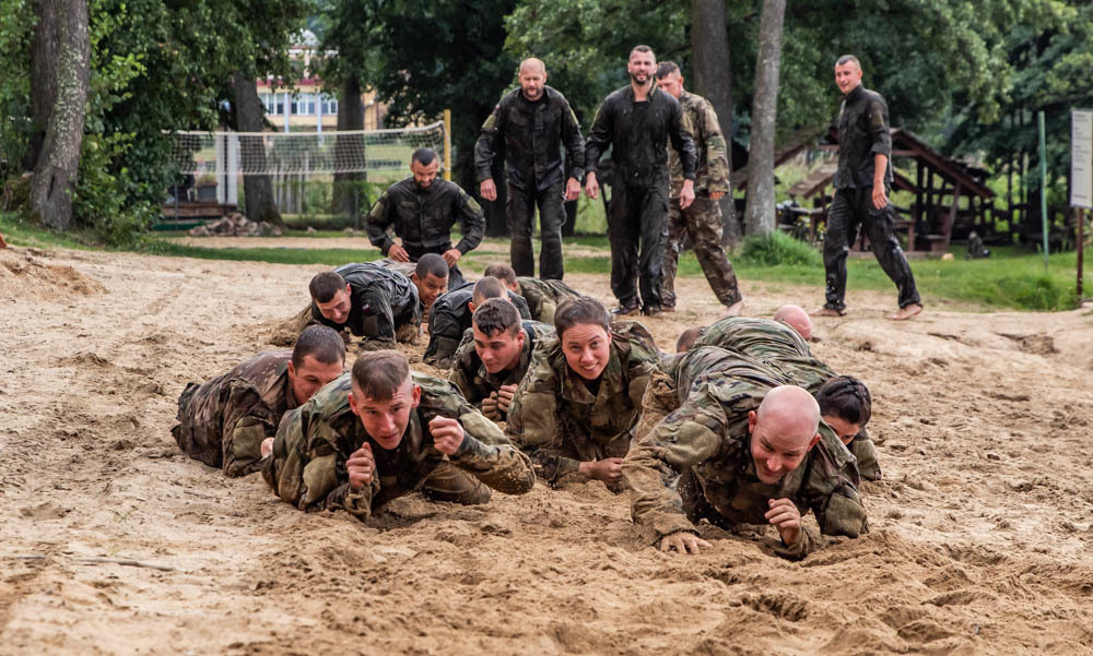 Soldiers from 278th Armored Cavalry Regiment along with Polish soldiers low crawl in the sand during day two of training for the water survival course hosted by 15th Mechanized Brigade in Gizycko, Poland, Aug. 12, 2019. (Tennessee National Guard)