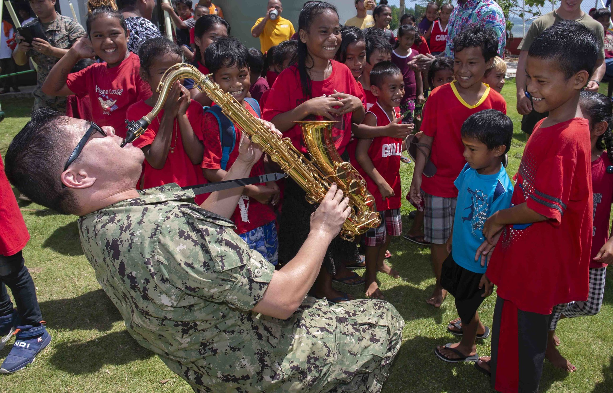 "Musician 1st Class Andrew Francisco, a member of the Pacific Partnership 2019 ""Black Sands"" Brass Band, plays the saxophone for the students of Sapone Elementary School in Micronesia on April 22, 2019, during a concert to enhance community relationships during Pacific Partnership 2019. (Mass Communication Specialist 3rd Class Chanel Turner/Navy)"