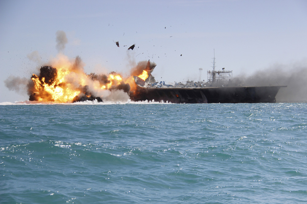 In this picture released by the Iranian Tasnim news agency on Wednesday, Feb. 25, 2015, a replica of a U.S. aircraft carrier is exploded by the Revolutionary Guard's speedboats during large-scale naval drills near the entrance of the Persian Gulf, Iran. The drill, named Great Prophet 9, was the first to involve a replica of a U.S. carrier. The Trump administration said Wednesday, Sept. 19, 2018 that a new U.S. State Department report cites Iran as the world's top sponsor of terrorism. (Tasnim News/AP)