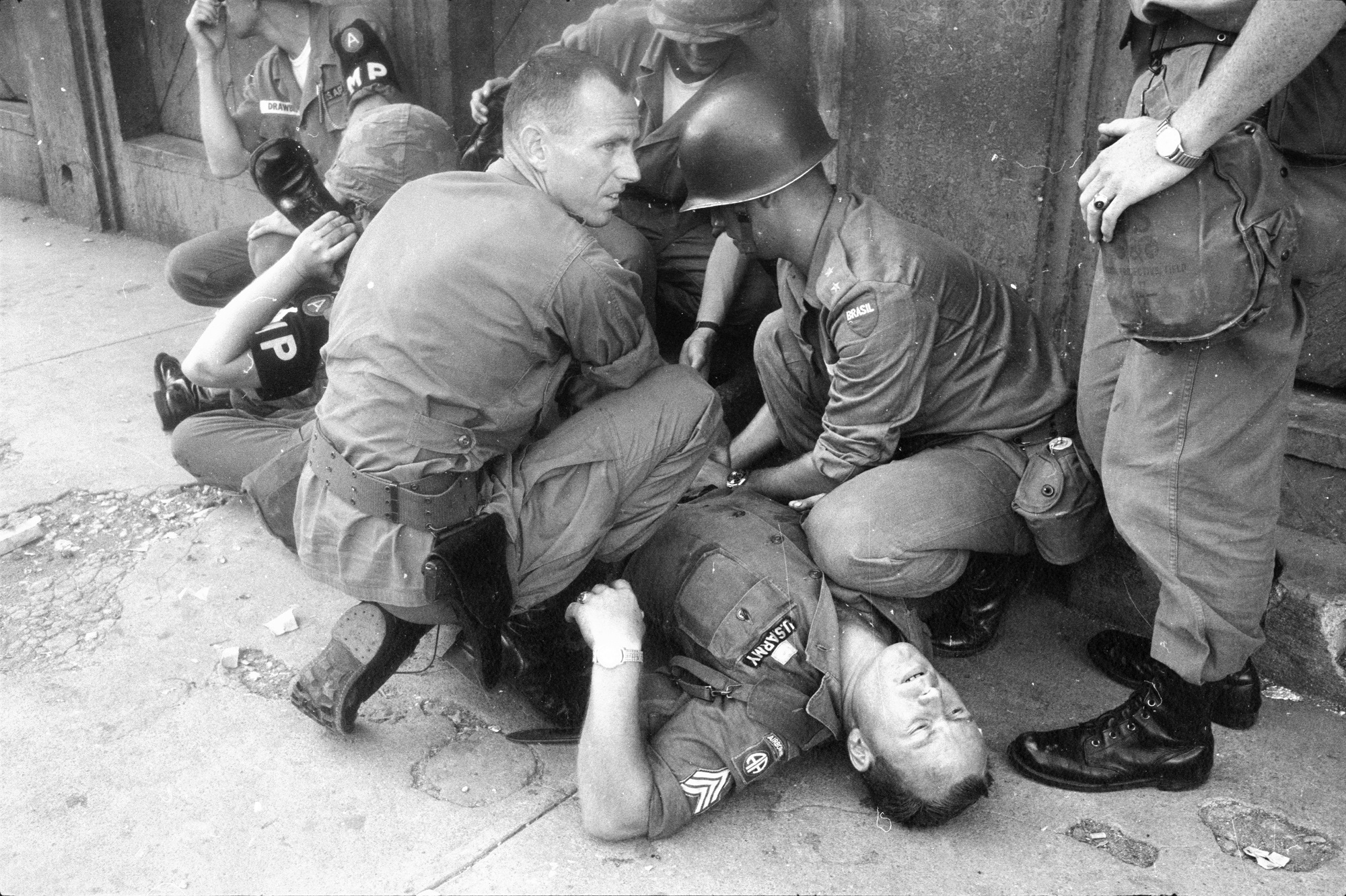 A U.S. paratrooper receives first aid from U.S. military police and a Brazilian officer while he waits for medics after being shot through the thigh by a rebel, Santo Domingo, Dominican Republic, 1965. (Wisconsin Historical Images 115429)
