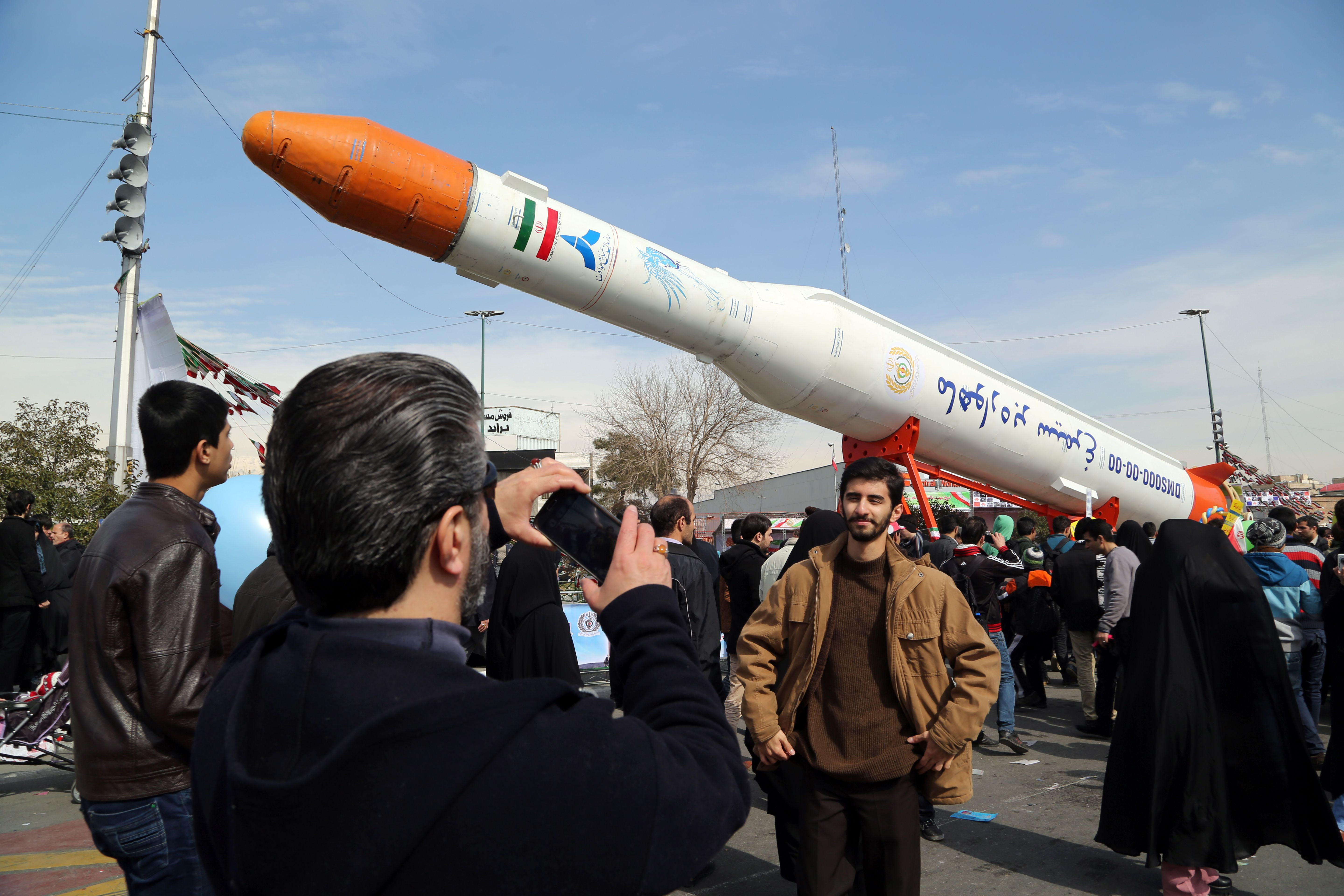 Iranians take pictures of the Simorgh (Phoenix) satellite rocket during celebrations in Tehran to mark the 37th anniversary of the Islamic Revolution on Feb. 11, 2016. (Atta Kenare/AFP via Getty Images)