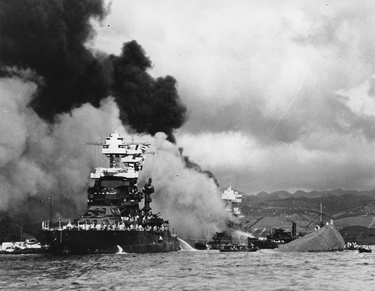 In this Dec. 7, 1941, file photo, part of the hull of the capsized USS Oklahoma is seen at right as the battleship USS West Virginia, center, begins to sink after suffering heavy damage, while the USS Maryland, left, is still afloat in Pearl Harbor, Oahu, Hawaii. (Navy via AP)