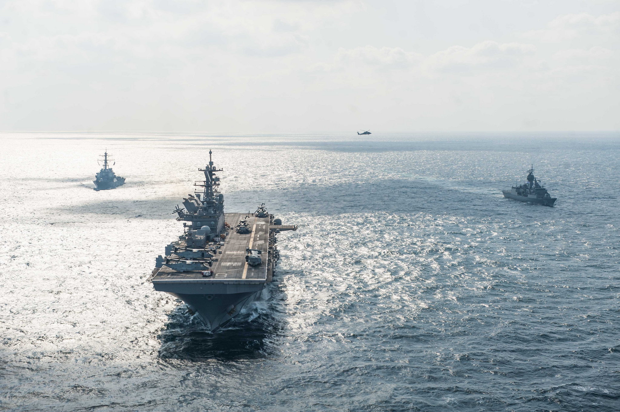 The amphibious assault ship USS America (LHA 6), center, the Arleigh Burke-class guided-missile destroyer USS Hopper (DDG 70), left, and the Anzac-class frigate HMAS Warramunga (FFH 152) steam in formation Nov. 28, 2017, while participating in a photo exercise in the Arabian Gulf. (MC2 Alexander Ventura II/Navy)
