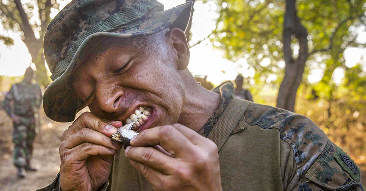 Marine 1st Sgt. Mauricio Grande, company First Sergeant of Kilo Company, Battalion Landing Team 3/1, 13th Marine Expeditionary Unit (MEU), bites into a cooked snake during Cooperation Afloat Readiness And Training (CARAT) Indonesia 2018. (Cpl. Danny Gonzalez/Marine Corps)
