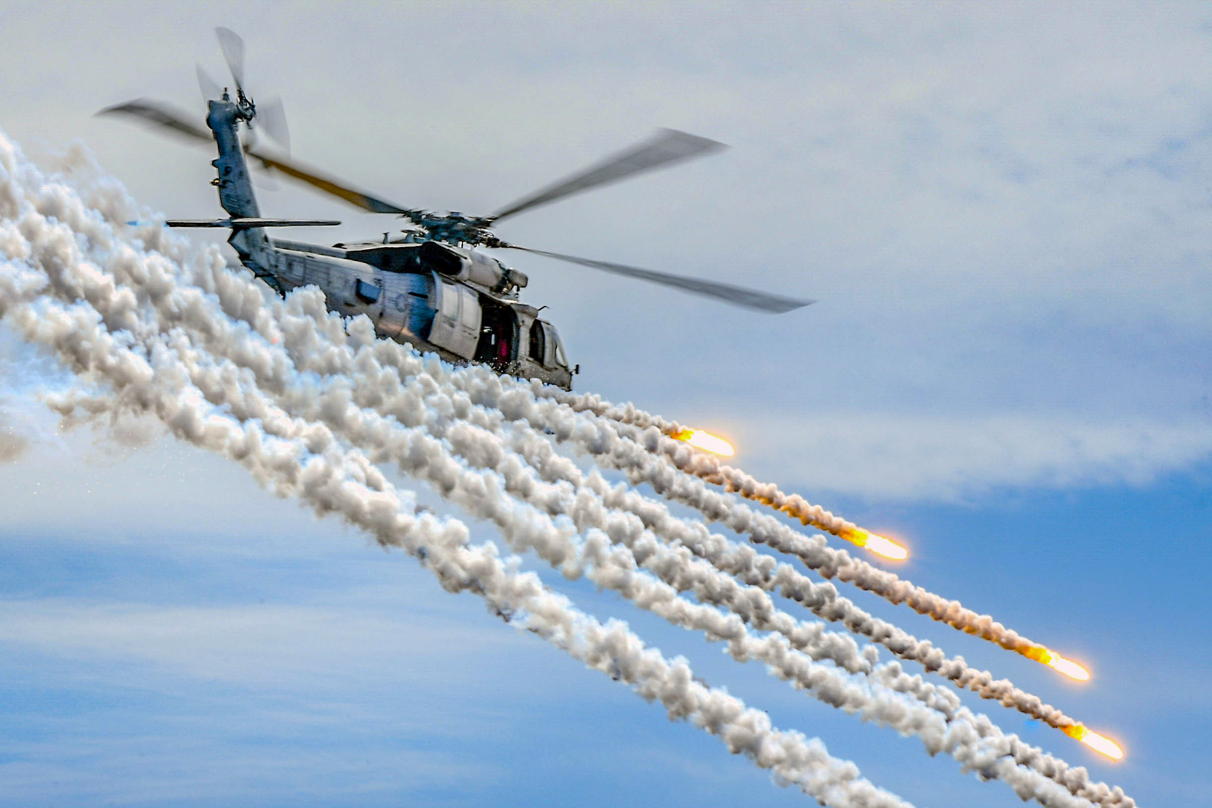 An MH-60S Sea Hawk, assigned to the Indians of Helicopter Sea Combat Squadron (HSC) 6, fires flares alongside the aircraft carrier USS Theodore Roosevelt (CVN 71) during an air power demonstration. Theodore Roosevelt is currently deployed in the Pacific Ocean. (U.S. Navy photo by Mass Communication Specialist Seaman Michael A. Colemanberry/Navy)