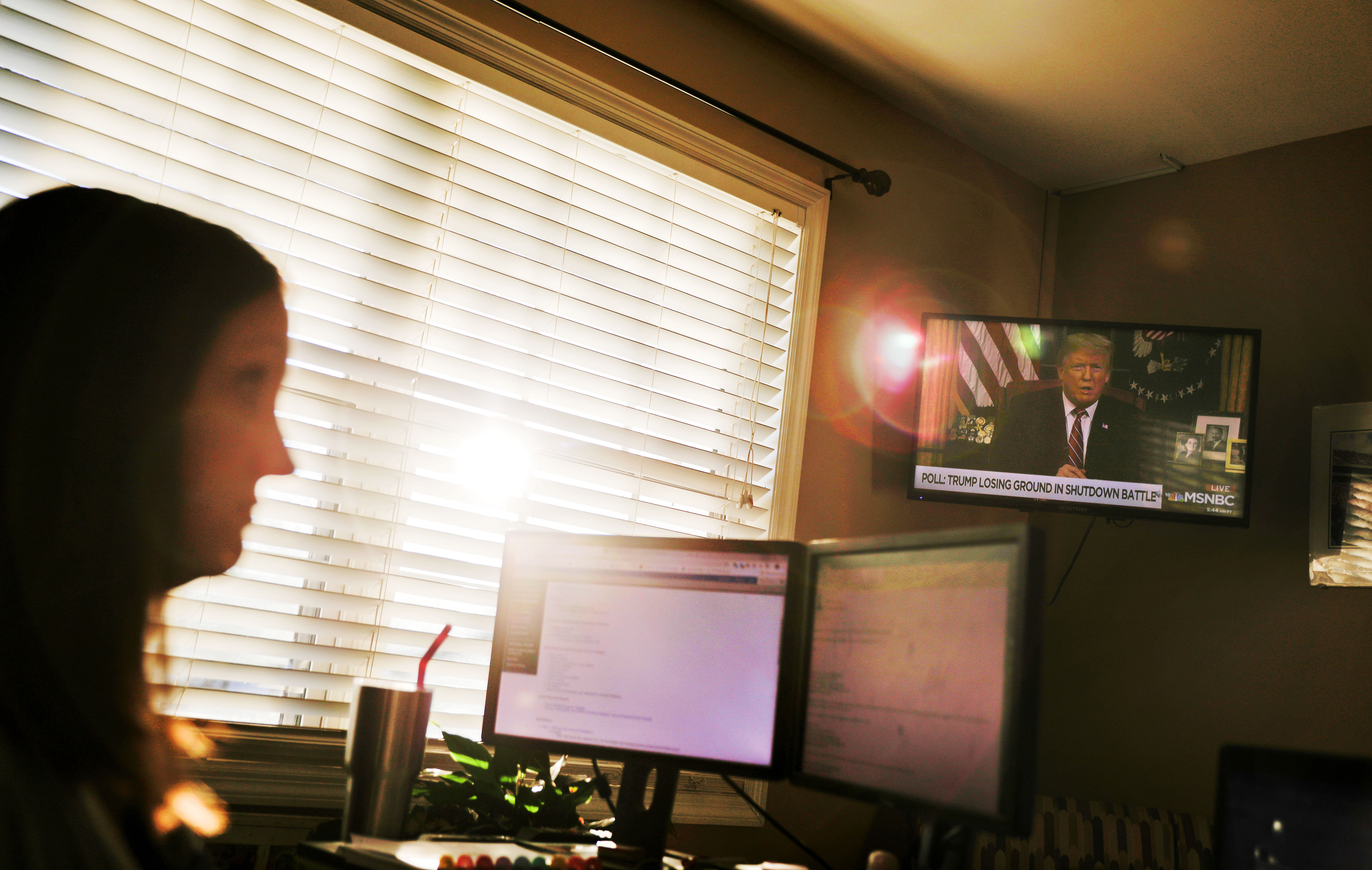 Katie Barron watches a rebroadcast of President Donald Trump's address to the nation on the partial government shutdown as she works from home in Madison, Ala., Wednesday, Jan. 9, 2019. Barron works for a private company not connected to the government but her husband is a National Weather Service meteorologist forced to work without pay because his job is classified as essential. (David Goldman/AP)