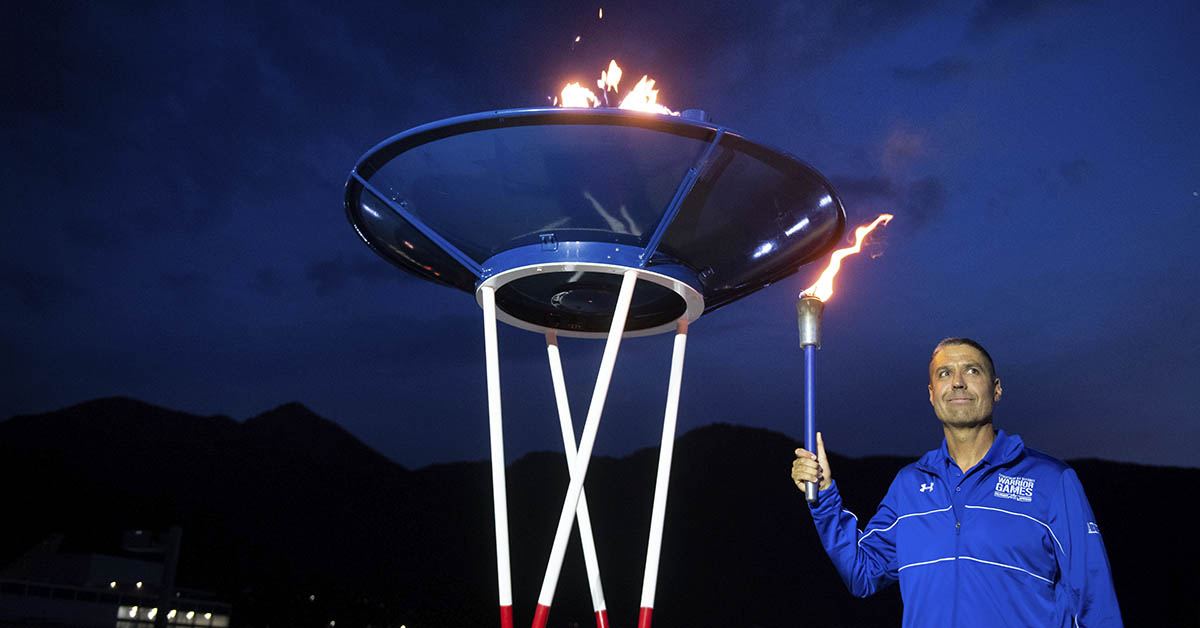 U.S. Air Force Master Sgt Shanon Hampton lights a torch from the cauldron during the Closing Ceremony at the 2018 Department of Defense Warrior Games June 9, 2018 at the Air Force Academy in Colorado Springs, Colo. (Mark Reis/DoD)