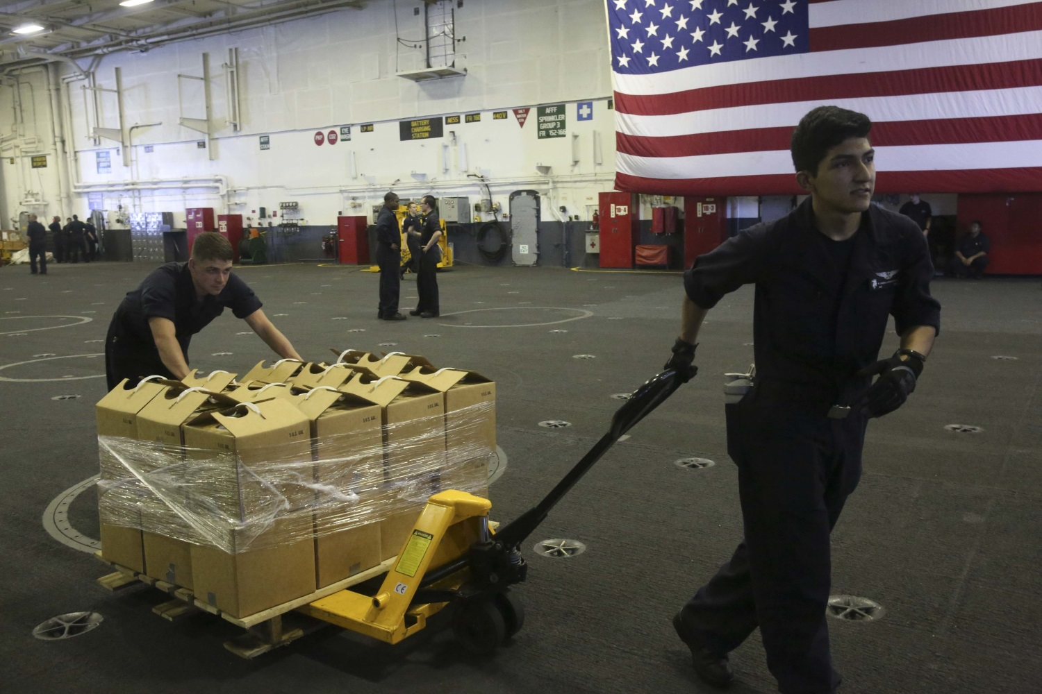 Sailors aboard the Nimitz-Class aircraft carrier USS Abraham Lincoln (CVN 72) move pallets of water on Sept. 11, 2017, in preparation to support those affected by Hurricane Irma. (Aviation Boatswain's Mate (Equipment) 2nd Class Lauren D. Smith/Navy)