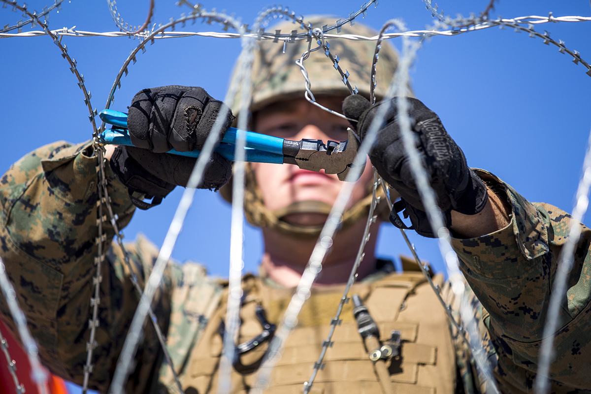 A U.S. Marine with 7th Engineer Support Battalion, Special Purpose Marine Air-Ground Task Force 7, secures concertina wire as part of a barricade at the California-Mexico border at the Otay Mesa Port of Entry in California. Some troops deployed to the border will be leaving this week. (Sgt. Brandon Maldonado/Marine Corps)