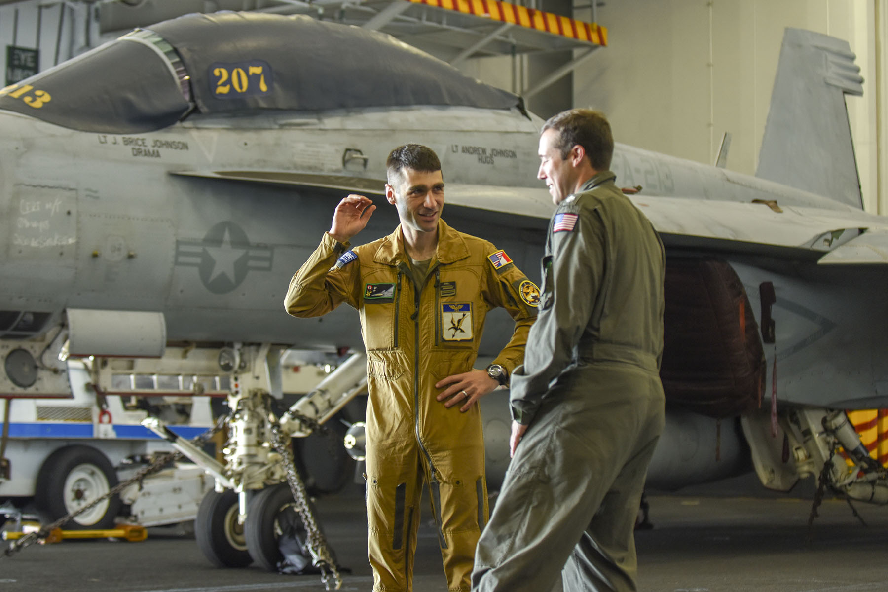 French Rafale pilot Vincent Isorce (L) and US Navy pilot Patrick Baker chat prior to a media session inside the hangar deck of the USS George H.W. Bush aircraft carrier on May 12, 2018 in the Atlantic Ocean - For ten days some 300 French sailors, including 16 pilots, their 12 Rafales fighter jets and one Hawkeye Surveillance plane are training on the USS George H.W. Bush aircraft carrier in the Atlantic ocean in what is been called the