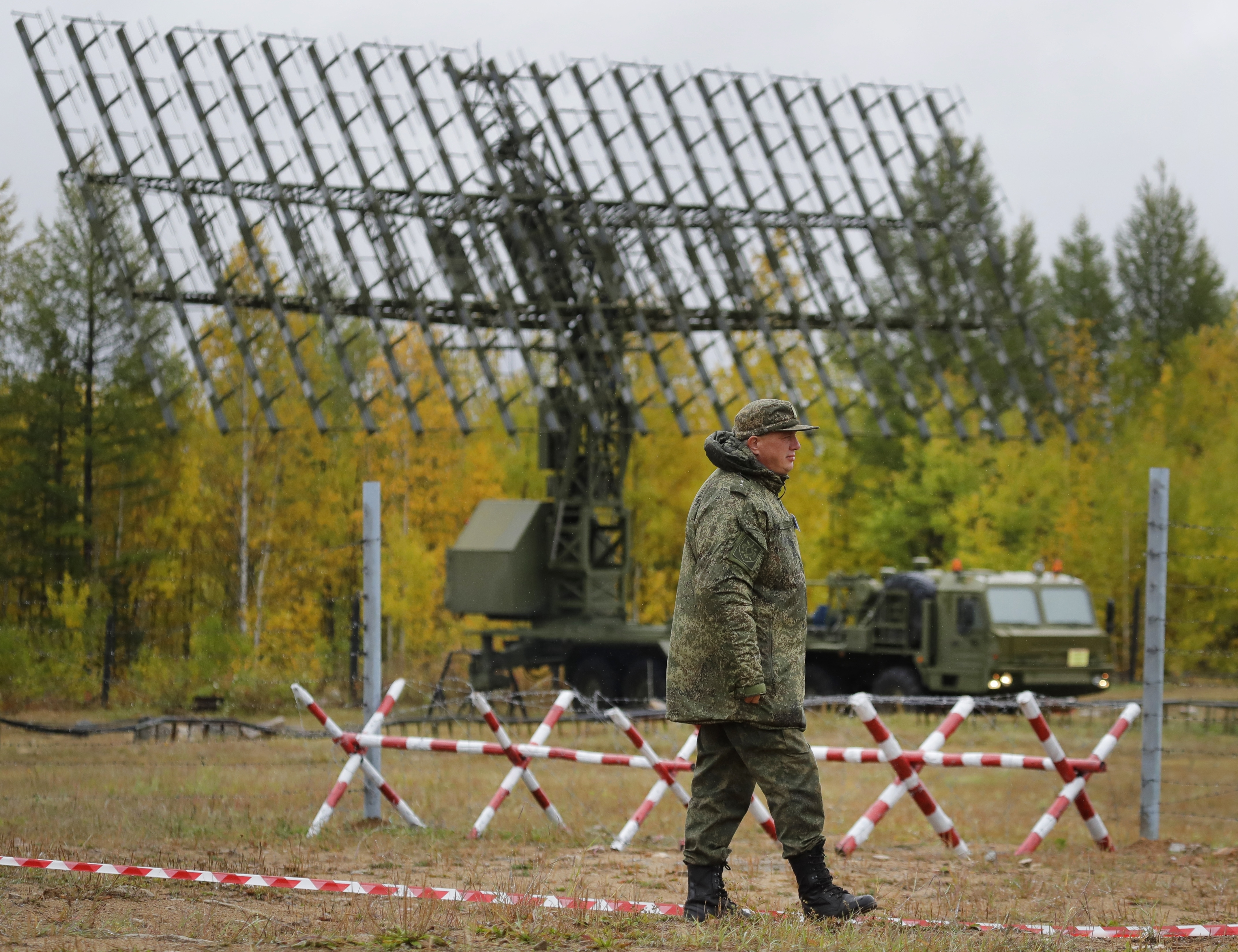 A Russian walks past a Nebo-M radar deployed in a forest, during a military exercises on training ground