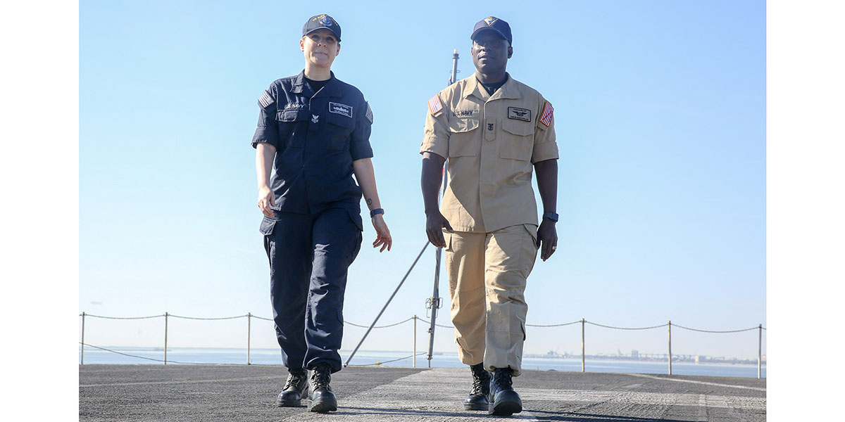 Yeoman 1st Class Kelly Pyron, assigned to U.S. Fleet Forces Command, and Force Master Chief Huben L. Phillips, assigned to commander, Naval Air Force Atlantic, demonstrate the operational wear ability of the flame-resistant, two-piece organizational clothing prototype aboard aircraft carrier USS Harry S. Truman (Mass Communication Specialist 2nd Class Stacy M. Atkins Ricks/Navy)