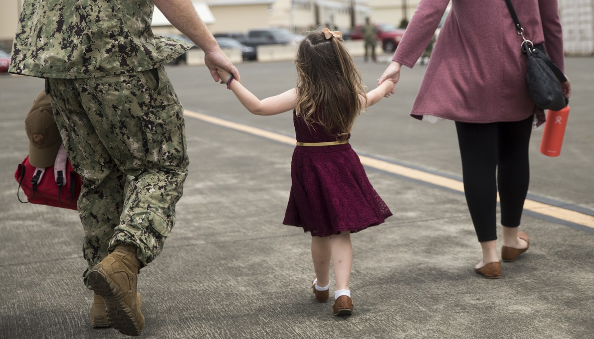 A U.S. sailor and his wife walk together while holding the hands of their daughter during an April homecoming. (Sgt. Alex Kouns/Marine Corps)