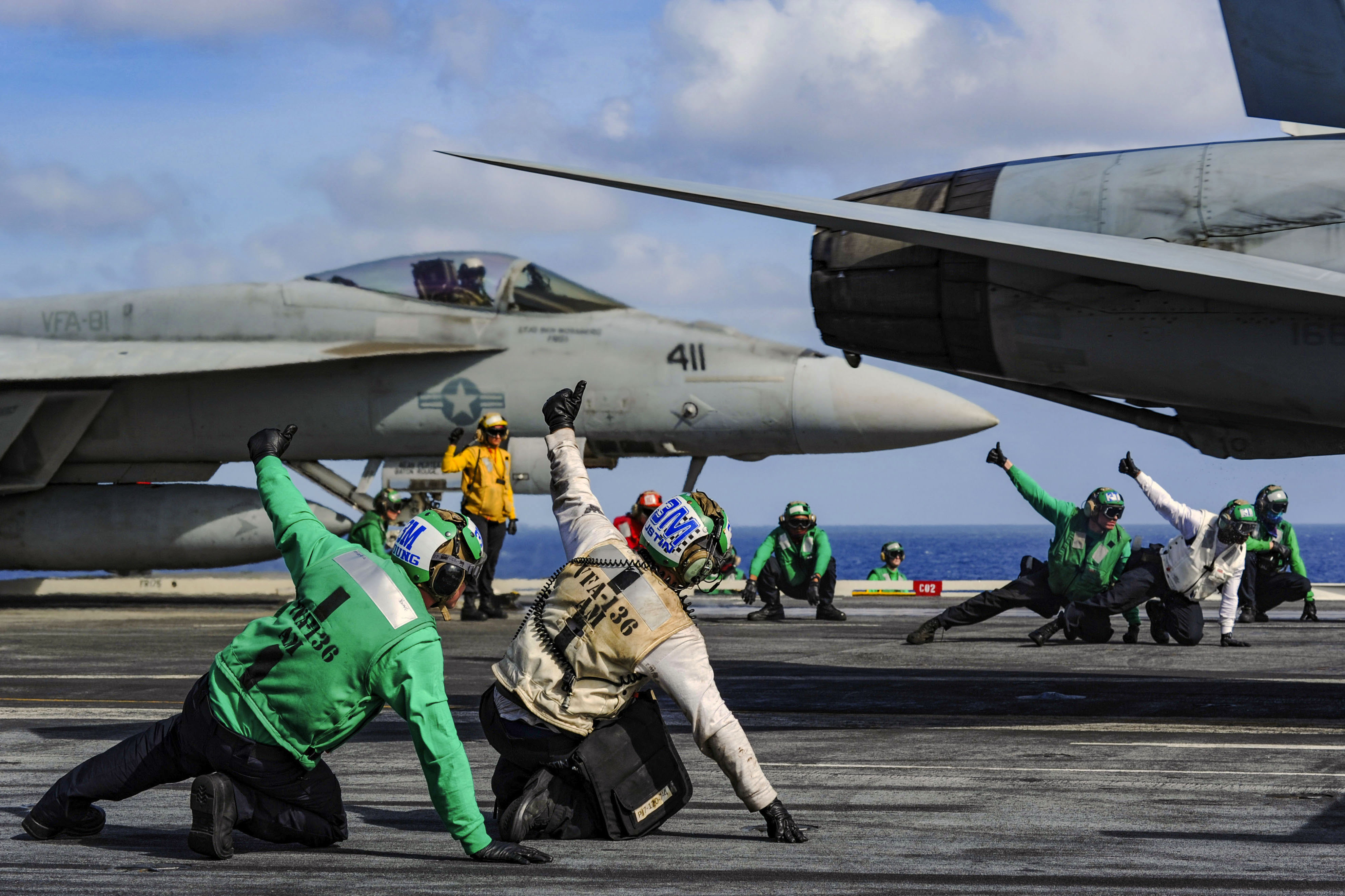 Sailors signal for the launch of an F/A-18E Super Hornet assigned to the