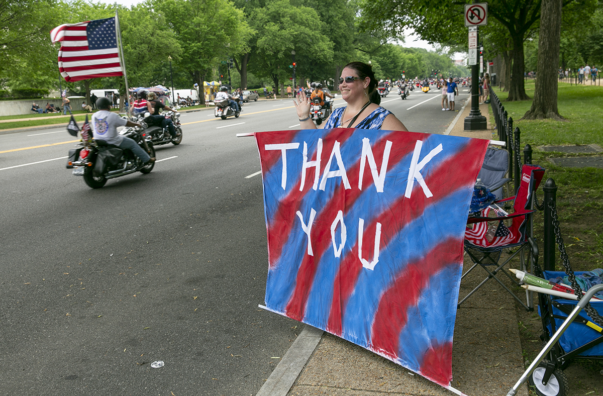 Susan McBride, from Maryland, thanks riders for their service during Rolling Thunder XXXI First Amendment Demonstration Run along Constitution Ave. in Washington, DC on Sunday May 27, 2018. Motorcycle riders from across the nation, rode a designated route through the Mall area of Washington, D.C. The event is an actual demonstration/protest to bring awareness and accountability for POWs and MIAs left behind.(Alan Lessig/Staff)