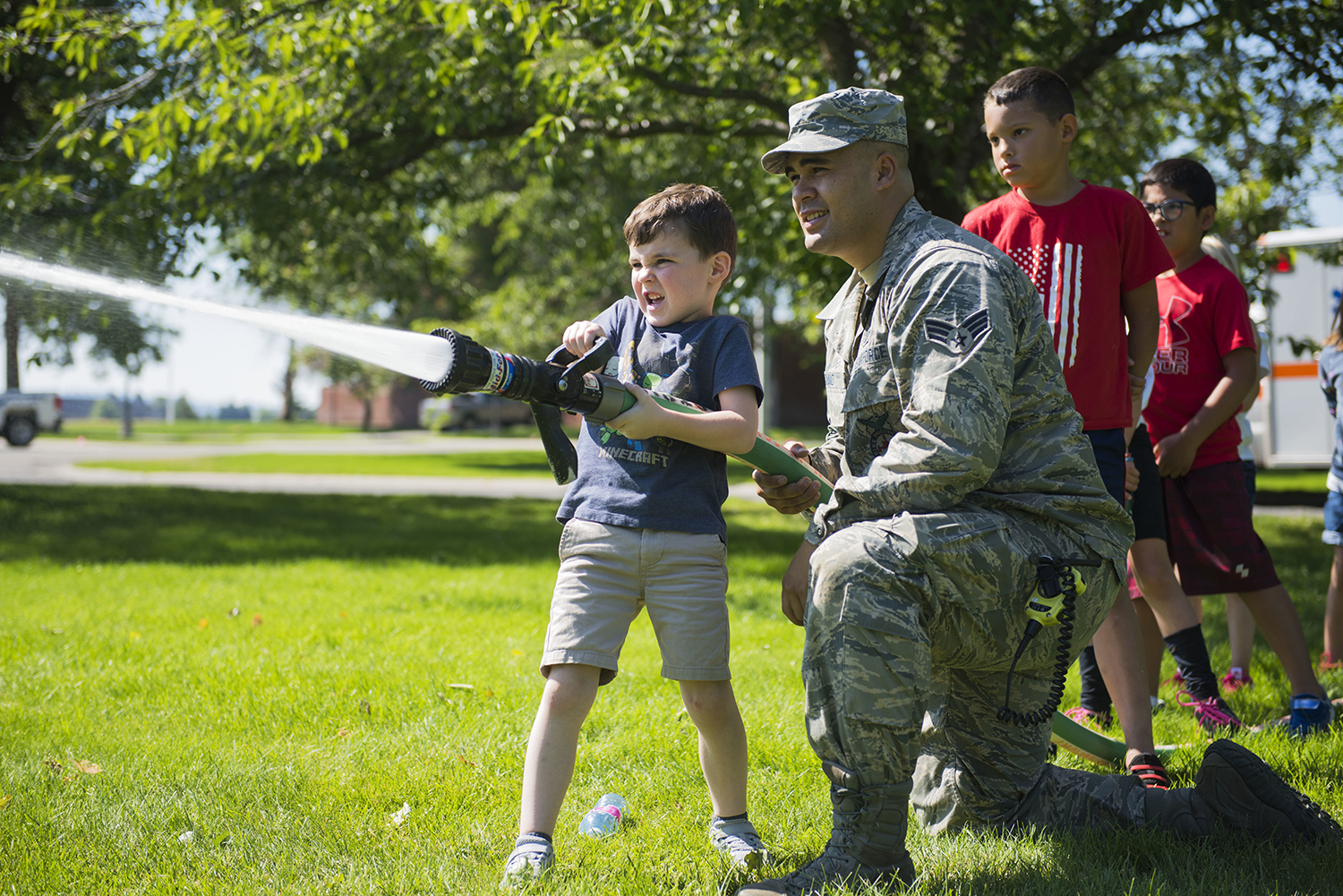 Senior Airman Isaiah Raiano helps a child operate a fire hose during the Summer Youth Fair at Fairchild Air Force Base, Wash., July 25, 2019. (Airman 1st Class Lawrence Sena/Air Force)