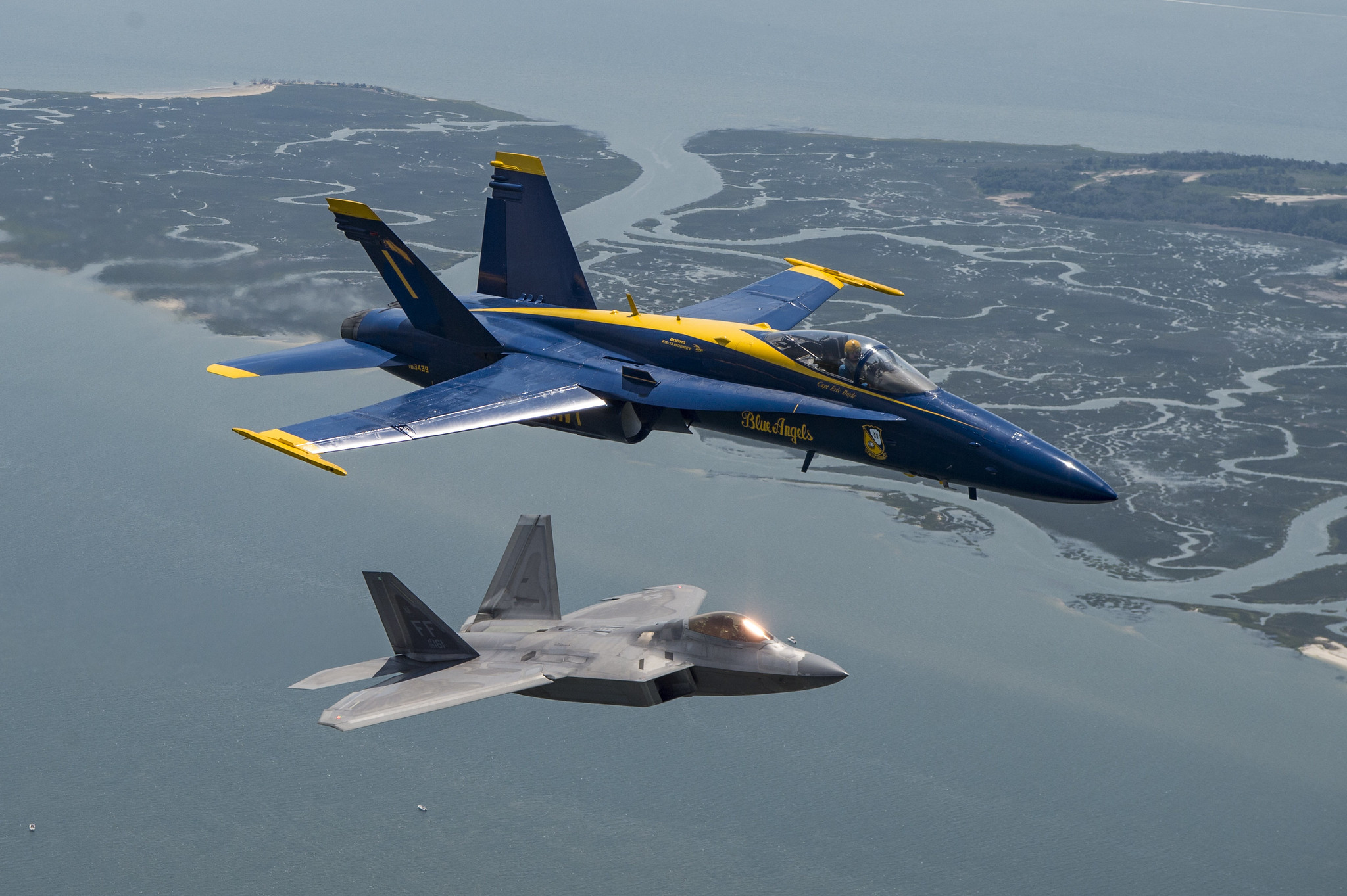 Capt. Eric Doyle, commanding officer of the U.S. Navy flight demonstration squadron, the Blue Angels, flies in formation with an F-22 Raptor assigned to the U.S. Air Force's F-22 Raptor demonstration team April 25, 2019, during a photo exercise above Marine Corps Air Station Beaufort. (Mass Communication Specialist 2nd Class Christopher Gordon/Navy)