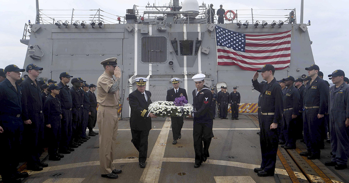 Cmdr. Todd Penrod, executive officer of the Arleigh Burke-class guided-missile destroyer USS Mustin (DDG 89), and Cryptologic Technician (Collection) 2nd Class Jared Ammon carry a wreath during a remembrance ceremony for USS Johnston (DD 557) aboard the ship. (MC2 Sonja Wickard/Navy)