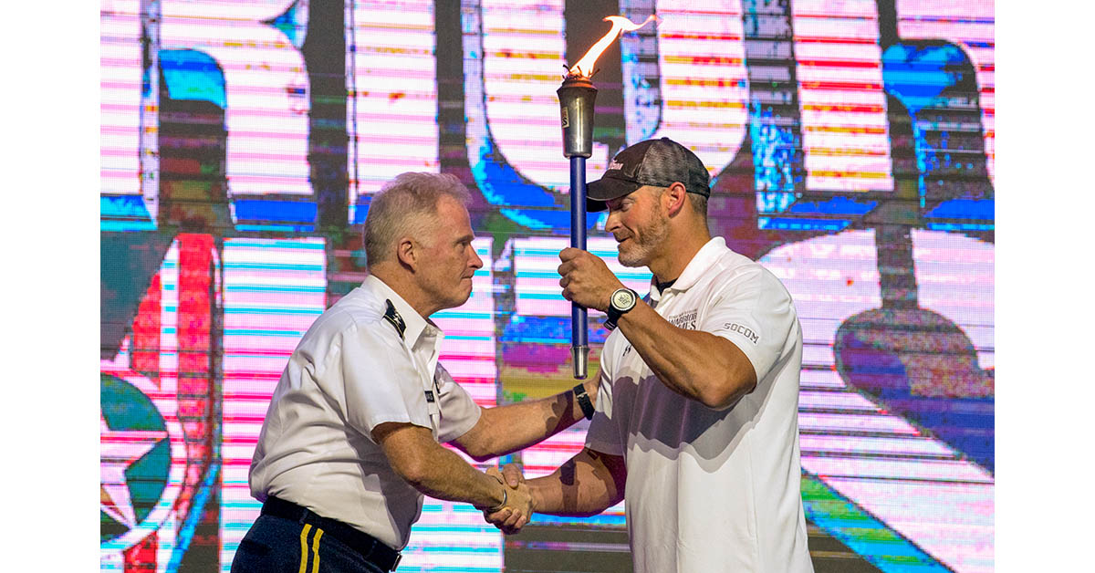 Team SOCOM Sgt. 1st Class Brant Ireland accepts the DoD Warrior Games torch from Special Operations Command Commander Gen. Raymond A. Thomas during closing ceremonies for the 2018 games at the Air Force Academy in Colorado Springs, Colo. June 9, 2018. (DoD photo by EJ Hersom)