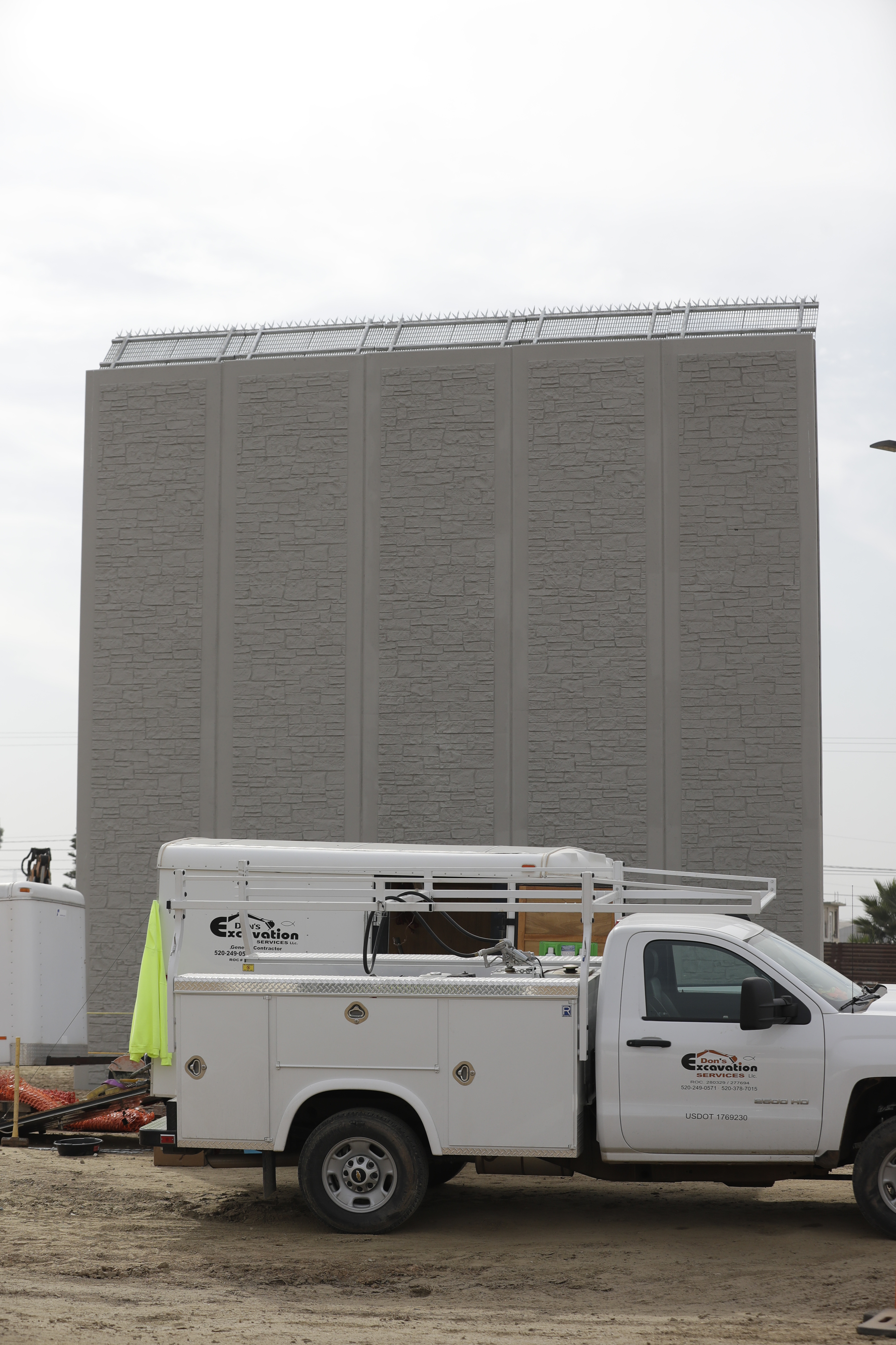 The wall by Texas Sterling Construction Company, based in Houston, Texas, has a contract value of $470,000. The gray surface of the U.S. side is stamped with patterns of different-sized bricks, like a driveway or sidewalk at an upscale home. There is a steel plate on top with prongs that feature at three metal spikes, resembling an agave plant. (Gregory Bull/AP)