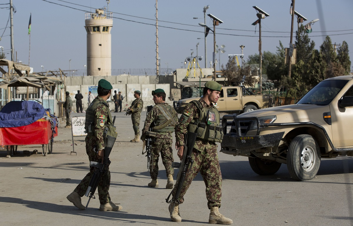 Afghan soldiers guard the main road to the Bagram Airfield main gate, north of Kabul, Afghanistan, Nov. 12, 2016. An Afghan worker detonated a suicide vest as troops gathered for a Veterans Day race, killing five and wounded 16. (Massoud Hossaini/AP)
