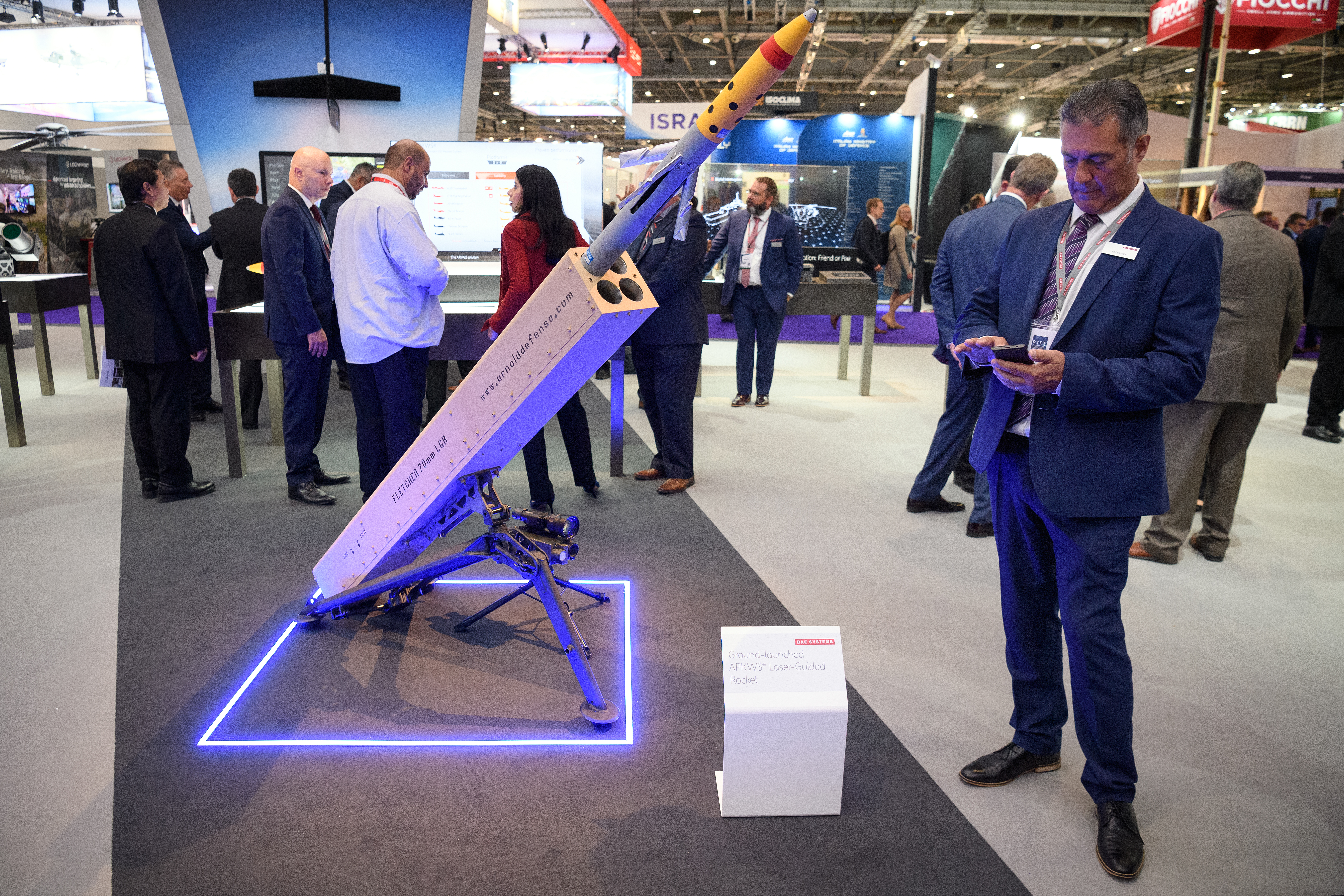 A man checks his phone as he stands next to the ground-based APKWS laser-guided rocket by BAE Systems on the second day of DSEI. (Leon Neal/Getty Images)