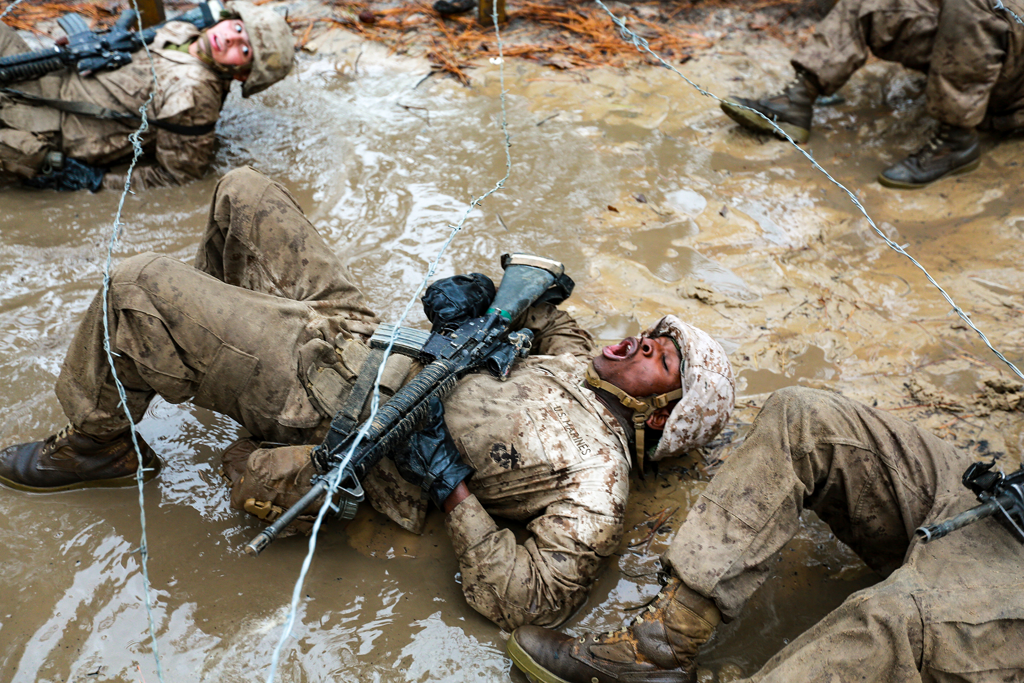 Recruits with Delta Company, 1st Recruit Training Battalion maneuver through mud and barbed wire during the Combat Endurance Course on Dec. 21, 2019, at Marine Corps Recruit Depot Parris Island, S.C. (Gunnery Sgt. Tyler Hlavac/Marine Corps)