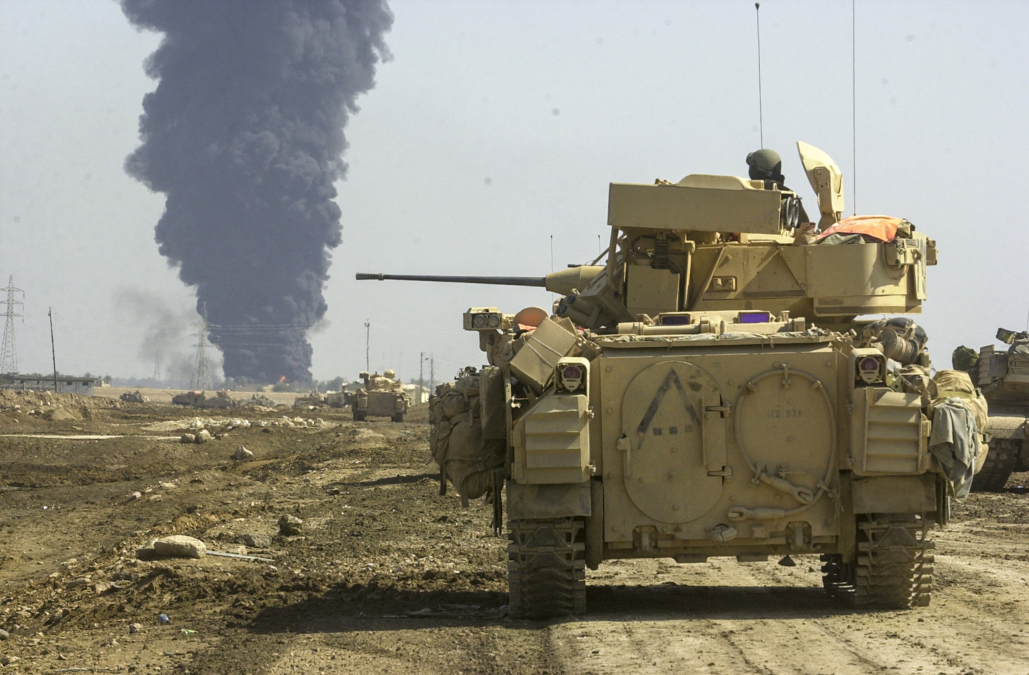 Troops from the U.S. Army's 3rd Squadron, 7th Cavalry Regiment watch as a target inside the village of As Samawah, Iraq goes up in flames. The Cavalry is in the process of taking the village and is receiving some resistance from fighters inside. (Warren Zinn/Army Times)