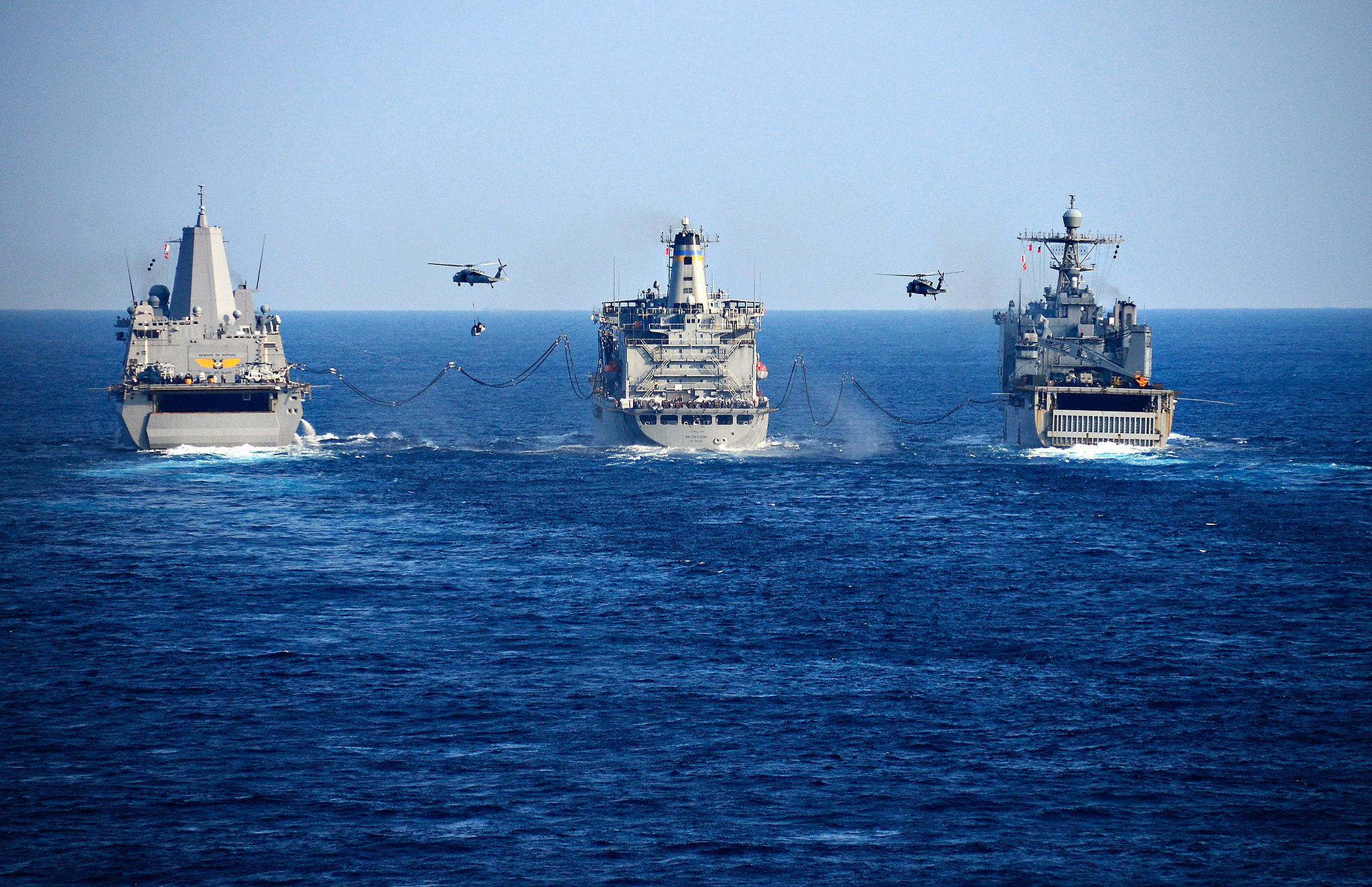 The transport dock ship USS Green Bay (LPD 20), the Military Sealift Command fleet replenishment oiler USNS Walter S. Diehl (T-AO 193), and the amphibious dock landing ship USS Ashland (LSD 48) conduct a replenishment-at-sea with MH-60S Seahawk helicopters on Jan. 30, 2019, in the Philippine Sea. (MC1 Daniel Barker/Navy)