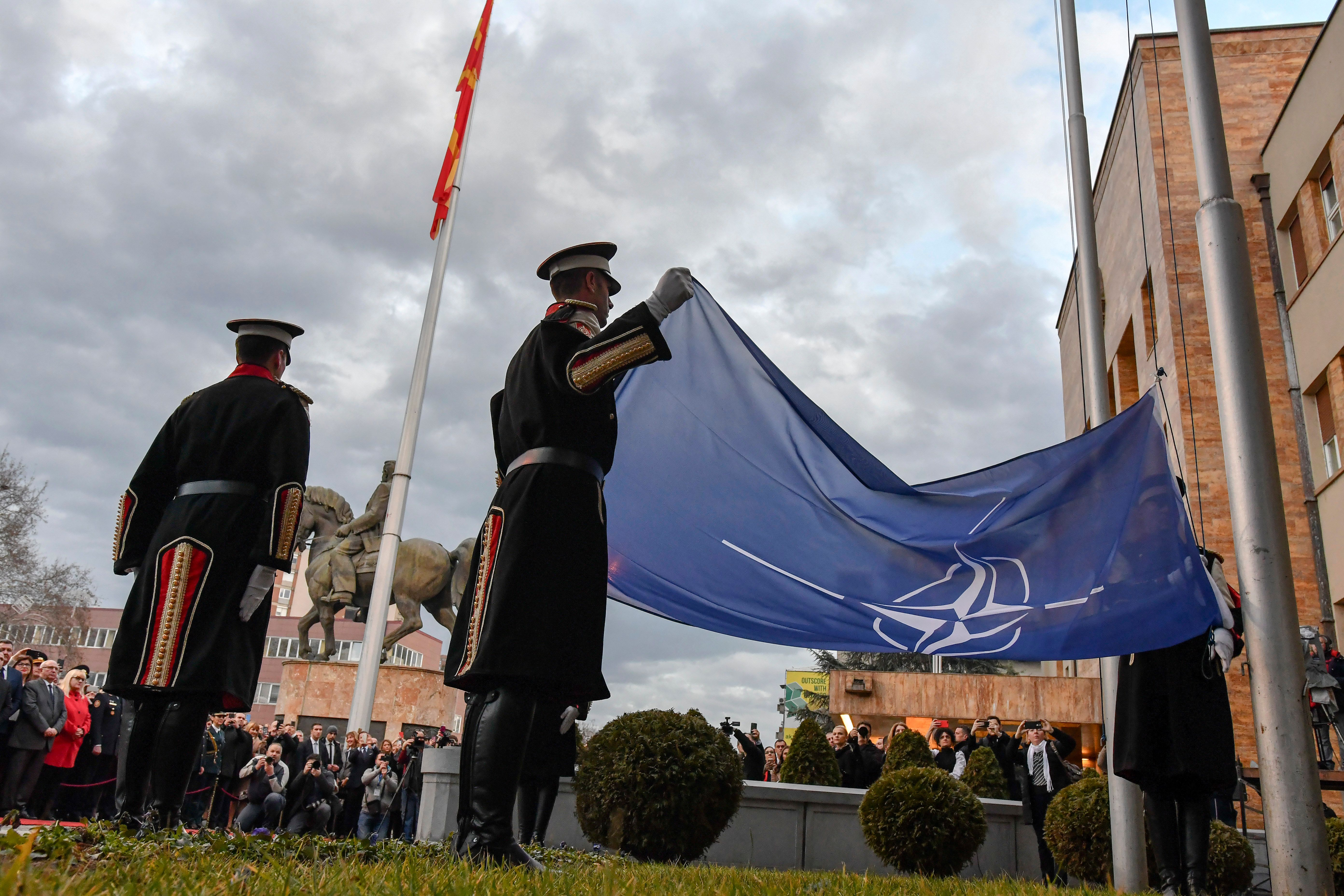 Members of the guard of honor raise the NATO flag during a flag ceremony in front of the parliament building in Skopje, North Macedonia, on Feb. 11, 2020, after the lawmakers ratified the NATO accession agreement. (Photo by Robert Atanasovski/AFP via Getty Images)