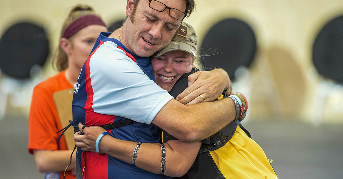 Team U.K. Lt. Cdr. Jason Saunders hugs Army Pfc. Lauren Jahn, who went on to win silver in recurve archery, during the 2018 DoD Warrior Games at the U.S. Air Force Academy in Colorado Springs on June 7, 2018. (Roger L. Wollenberg/DoD)