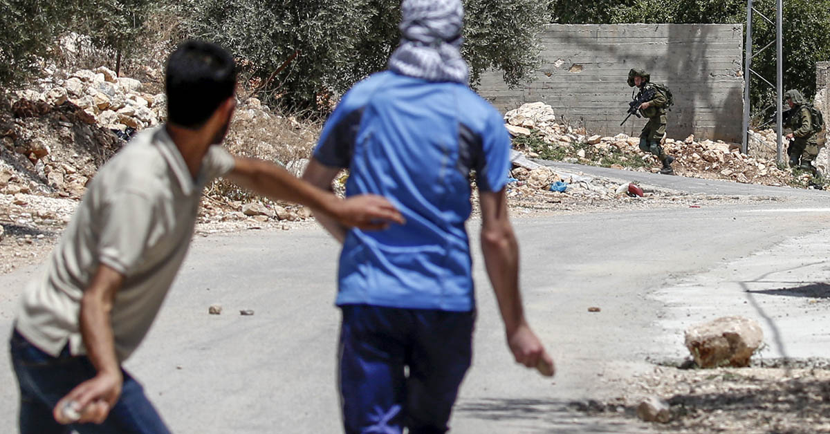 Palestinian protesters throw stones during clashes with Israeli soldiers following a weekly demonstration against the expropriation of Palestinian land by Israel in the village of Kfar Qaddum, near Nablus in the occupied West Bank, on June 8, 2018. (Jaafar Ashtiyeh/AFP via Getty Images)