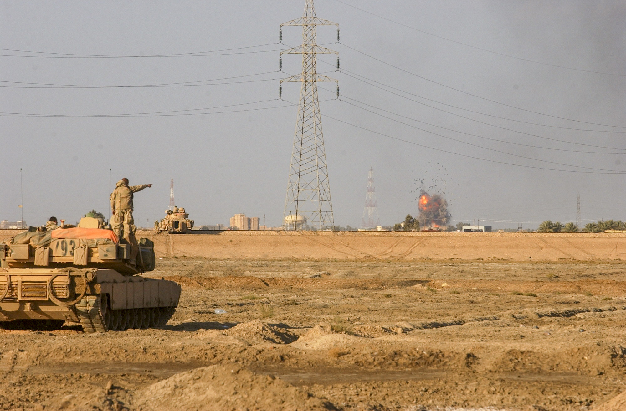 Soldiers from the U.S. Army's 7th Cavalry Regiment, watch on as a bomb from an F-16 blows up what was a headquarters for the Iraqi's that were fighting them. The troops have been operating around As Samawah for almost two days now and have been facing some strong resistance from the fighters inside. (Warren Zinn/Army Times)