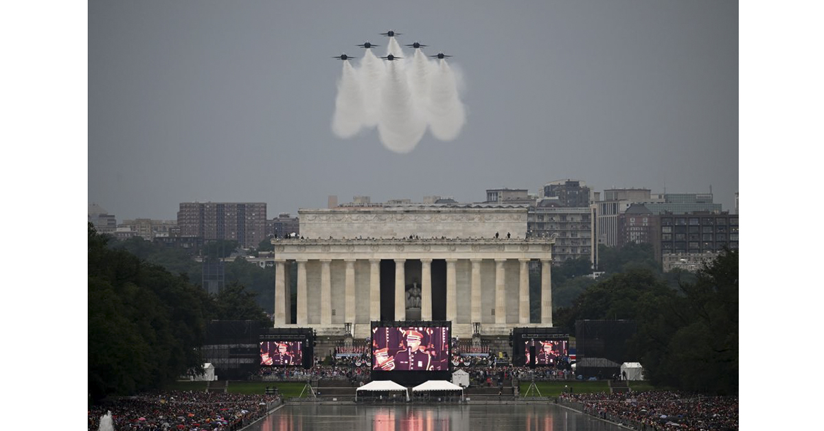 The U.S. Navy Blue Angels fly overhead as people gather on the National Mall during the