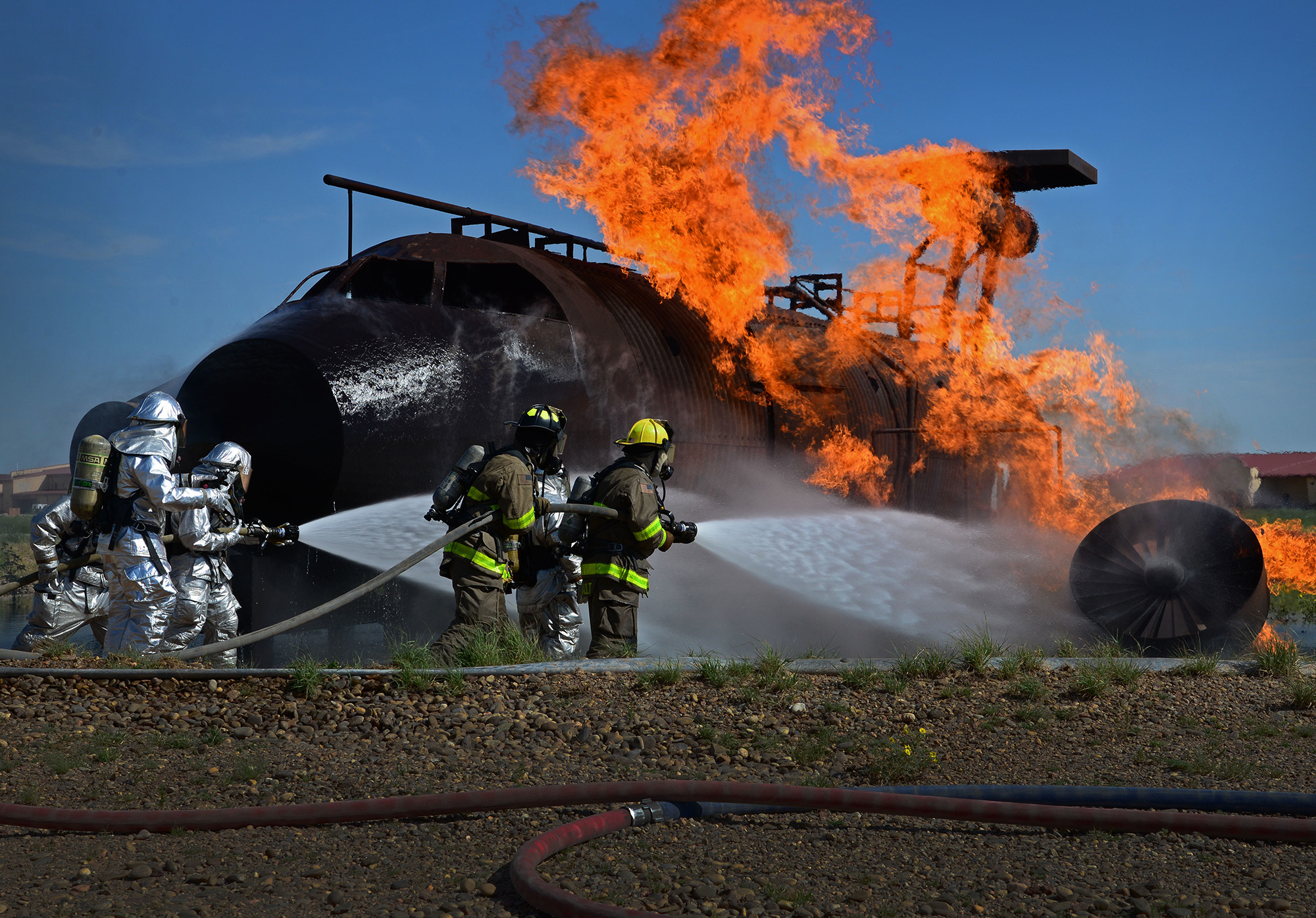 Air commandos with the 27th Special Operations Civil Engineer Squadron and Clovis, N.M., firefighters work together to put out a simulated aircraft fire during an exercise Aug. 14, 2015, at Cannon Air Force Base, N.M. (Staff Sgt. Alexx Mercer/Air Force)