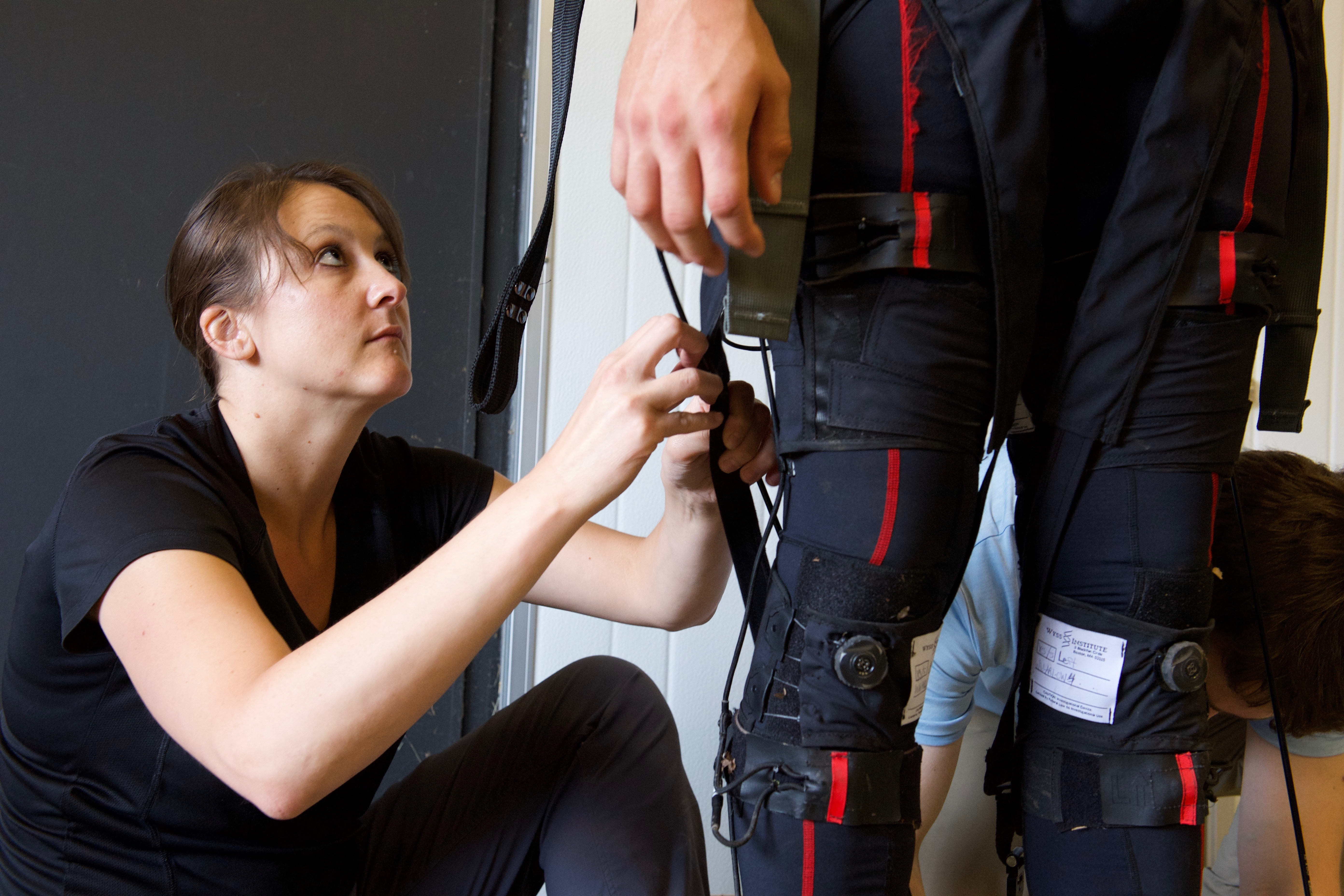 Dr. Courtney Webster makes adjustments to the Warrior Web physical augmentation suit from Harvard's Wyss Institute in Boston, Massachusetts. The project is one of many funded by DARPA, and is an example of a technology that could have both military and civil purposes. (David McNally/U.S. Army)
