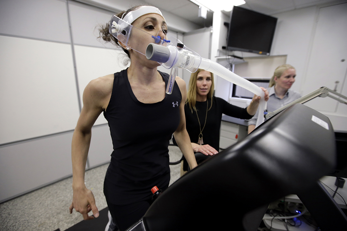 In this April 23, 2019, photo, research scientist Leila Walker, left, is assisted by nutritional physiologist Holly McClung, center, as they demonstrate equipment designed to evaluate fitness levels in female service members, not shown, who have joined elite fighting units such the Navy SEALs, at the U.S. Army Research Institute of Environmental Medicine, at the U.S. Army Combat Capabilities Development Command Soldier Center, in Natick, Mass. (Steven Senne/AP)