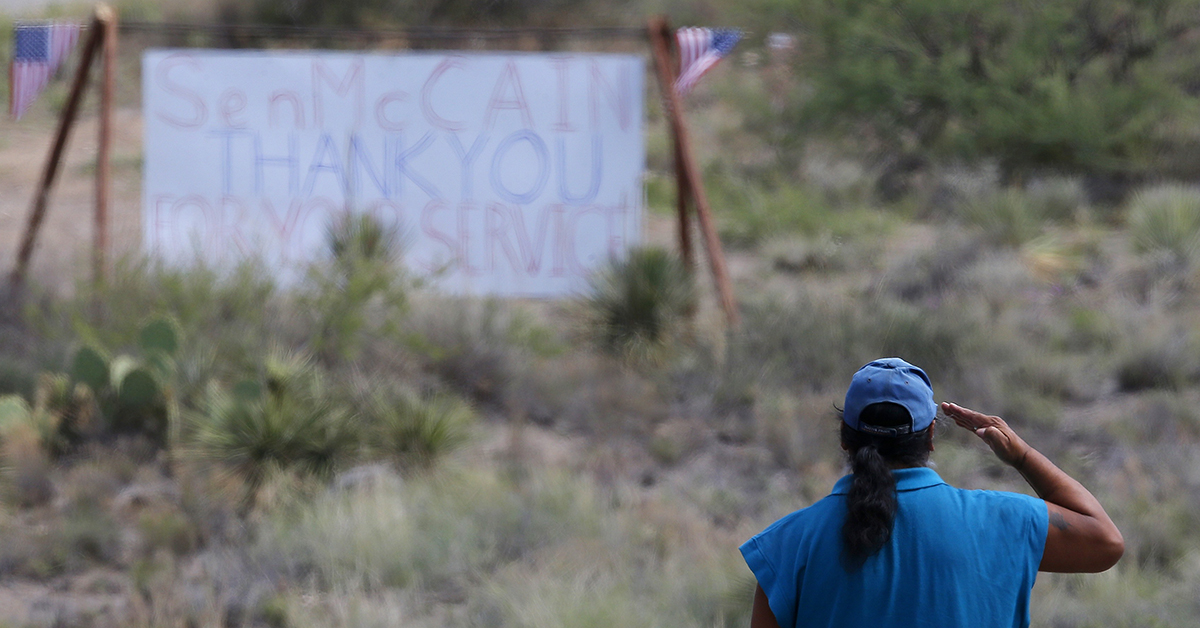 A military veteran pays his respects at the entrance to the Sen. John McCain's ranch complex in Cornville, Ariz., Saturday, Aug. 25, 2018. Sen. McCain, the war hero 2008 presidential candidate, passed away Saturday after a battle with brain cancer. (AP Photo/Ross D. Franklin)