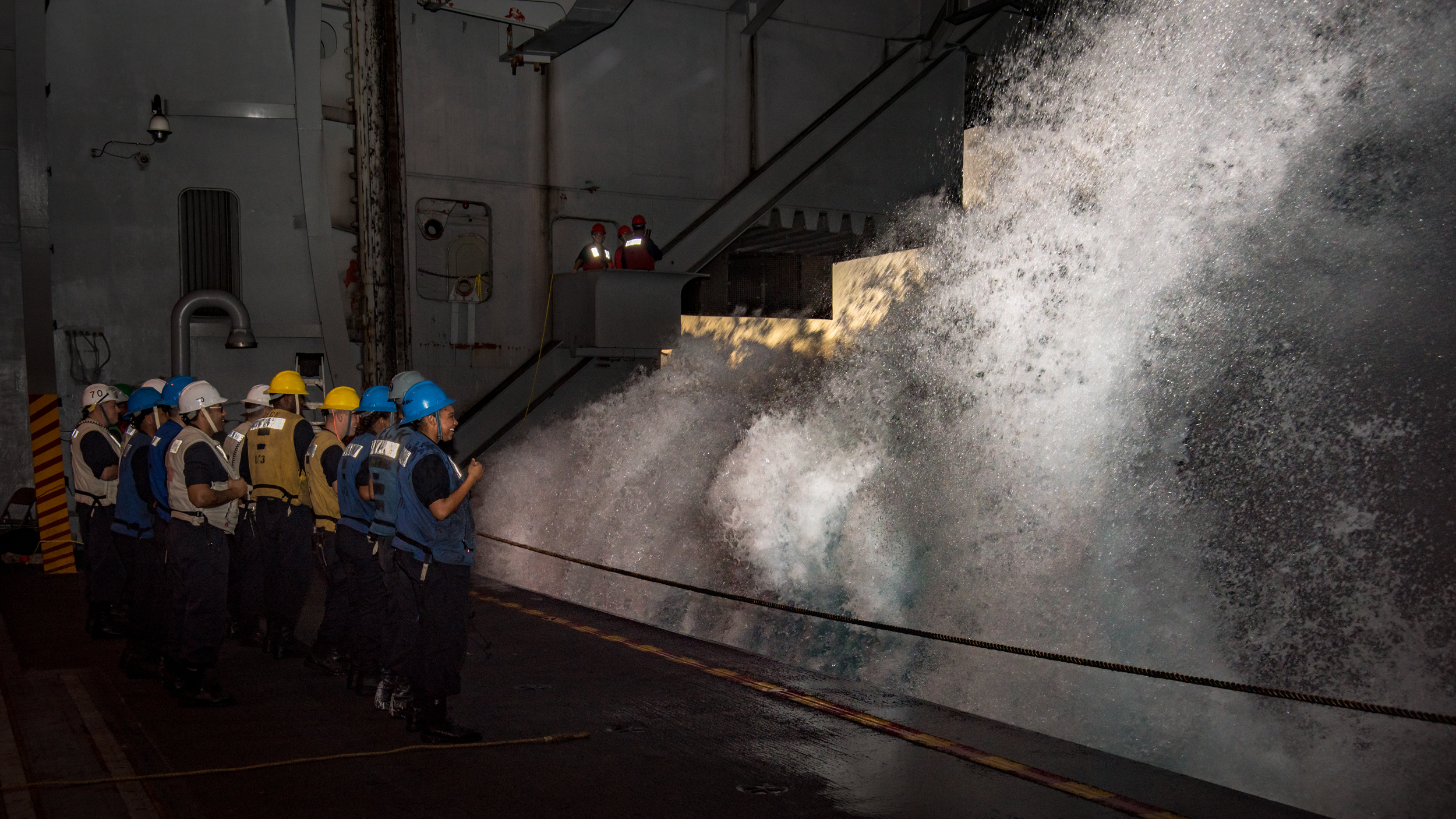 Sailors aboard Nimitz-class aircraft carrier USS Carl Vinson (CVN 70) watch as a wave crashes into the hangar bay during a replenishment-at-sea with Fleet Replenishment Oiler USNS Yukon (T-AO 202). U.S. Navy Photo by Mass Communication Specialist 3rd Class Kurtis A. Hatcher