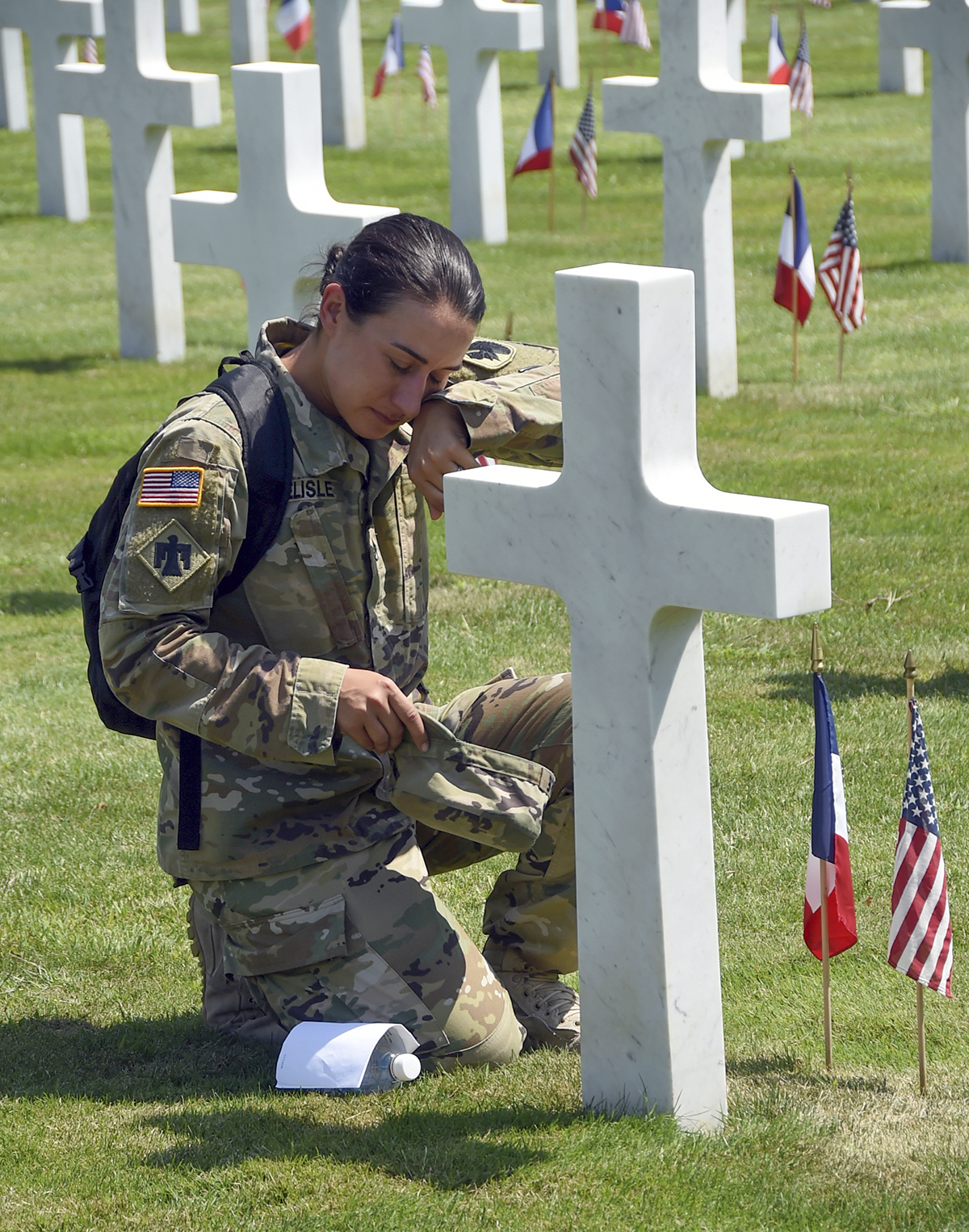 Staff Sgt. Ashley Delisle, Oklahoma Army National Guard state awards manager, wipes tears from her face after discovering the final resting place of her great uncle, Pvt. 1st Class Anton J. Reida, at the Oise-Aisne American Cemetery, Fere-En-Tardenois, France, July 27. Reida was killed during WWI on the Aisne-Marne battlefield, Sept. 1, 1918. Soldiers from units that comprised the 42nd Division during WWI participated in the second phase of a year-long WWI Centennial Commemoration across Northern France. (Sgt. Brian Schroeder/Oklahoma National Guard)