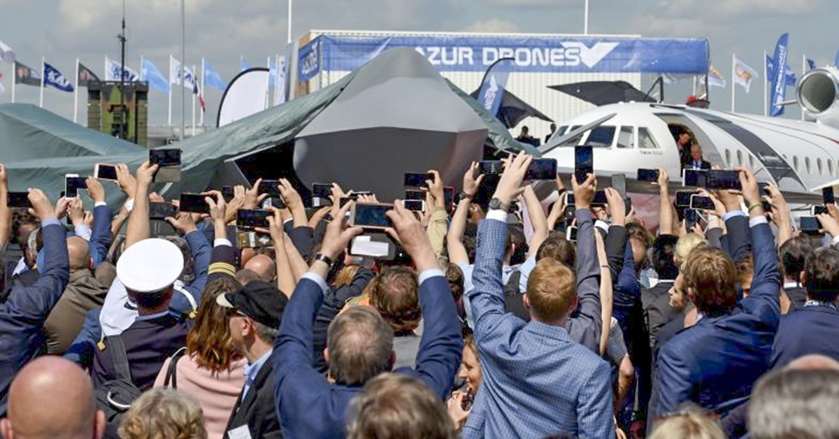 Visitors attend the unveiling ceremony of the full-scale jet fighter model of the the Franco-German-Spanish Future Combat Air System at the Paris Air Show on June 17, 2019. (Eric Piermont/AFP via Getty Images)