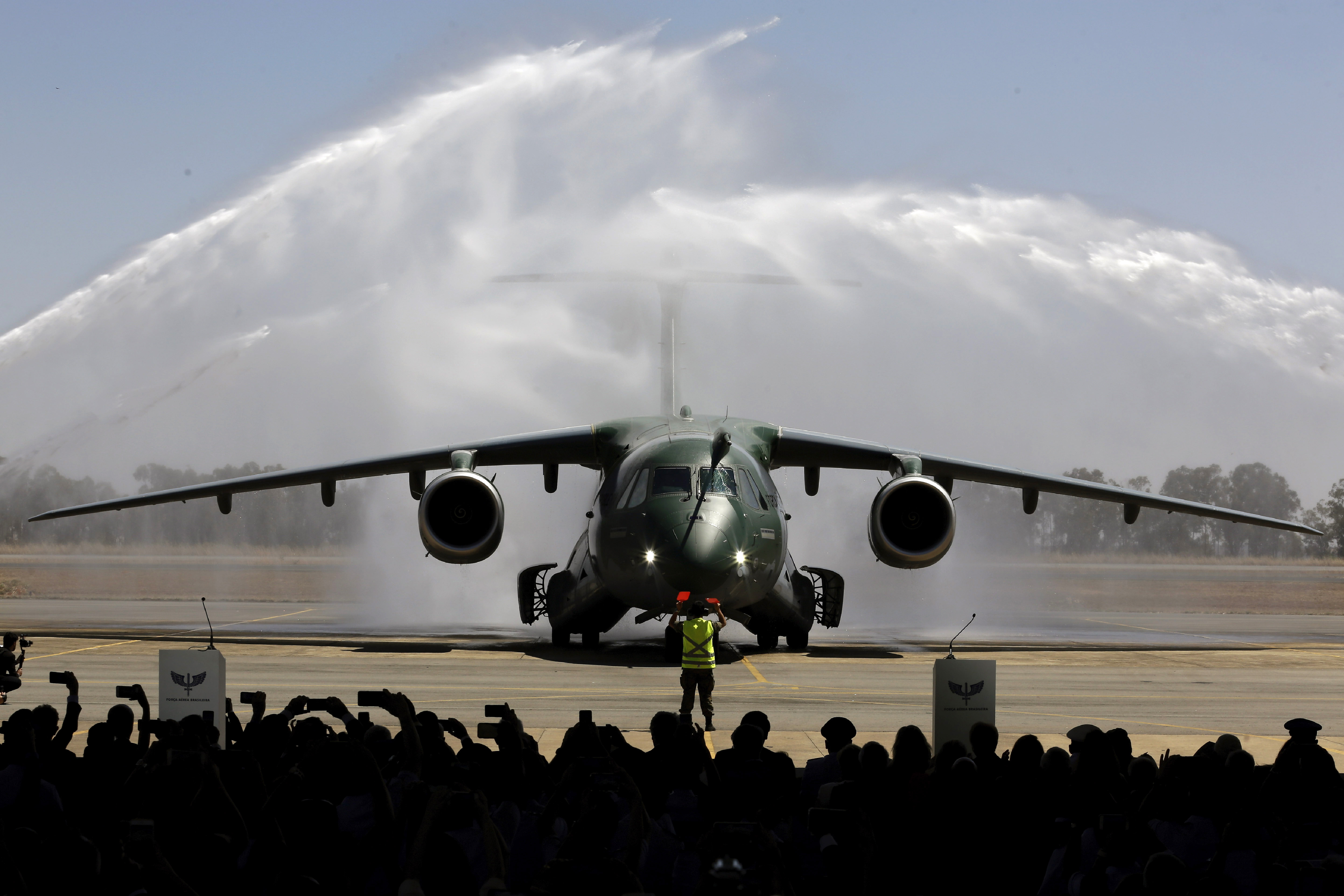 Plumes of water form arches over a KC-390 plane during a water salute at the air base in Anapolis, Brazil, Wednesday, Sept. 4, 2019. The new aircraft is capable of transporting and launching cargo and troops, as well as a wide range of missions: air evacuation, search and rescue, firefighting, air refueling and humanitarian aid. (AP Photo/Eraldo Peres)