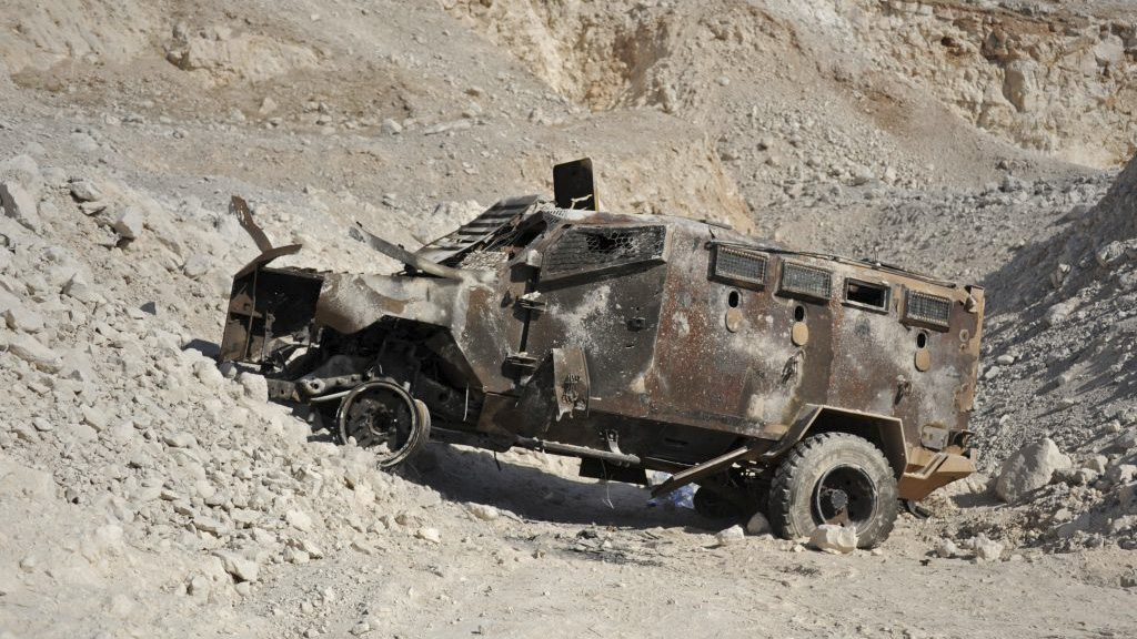 This picture taken on September 25, 2019 reportedly shows a destroyed armored vehicle near the entrance of a cave and tunnel system reportedly used by Syrian anti-government fighters near al-Lataminah in Hama province. - According to the Russian army, this vast underground network was used as a military base and habitation quarters by rebel fighters and as a workshop for making drones, and was abandoned as pro-government forces advanced on the area. (MAXIME POPOV/AFP/Getty Images)