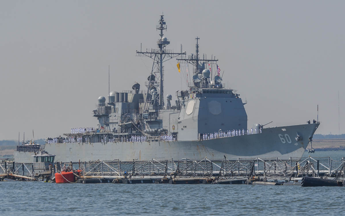 Norfolk, Va. (April 11, 2018) The guided-missile-crusie Normandy steams past Naval Station Norfolk's pier 14 on its way to its way to the Atlantic Ocean for her deployment with the Harry S. Truman battle group. (photo by Harold J. Gerwien)