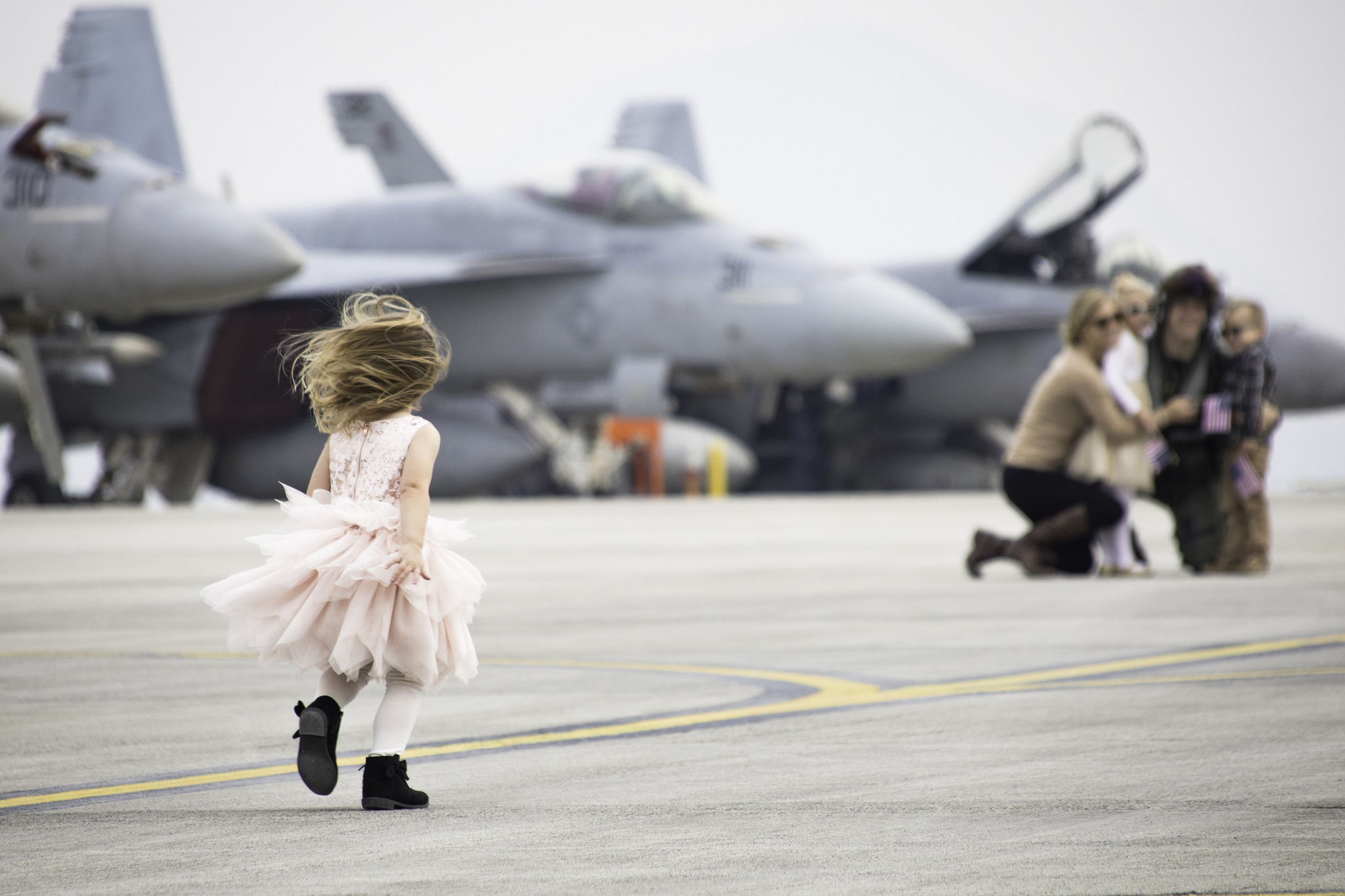 A young girl runs to greet her family after the arrival of Strike Fighter Squadron (VFA) 115, VFA-195 and Electronic Attack Squadron (VAQ) 141 at Marine Corps Air Station (MCAS) Iwakuni, Japan. VFA-115, VFA-195 and VAQ 141 arrived at MCAS Iwakuni as part Carrier Air Wing (CVW) 5's relocation from Naval Air Facility (NAF) Atsugi, Japan. (Cpl. Joseph Abrego/Marine Corps)